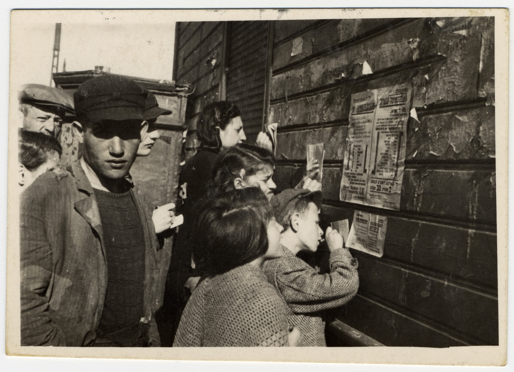 """A crowd reads a ghetto announcement about food rations tacked to a wall and copies down the information.  The original Yiddish caption reads: """"They copy rations from the wall.  They announce good news, but the goods are already long gone."""""""