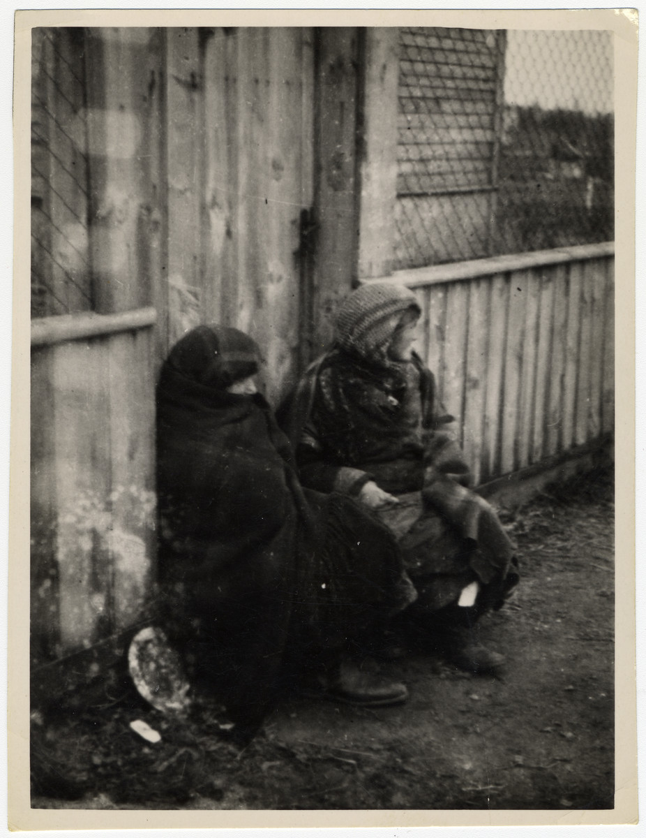 Two destitute women sit against a fence in the Lodz ghetto wrapped in blankets.