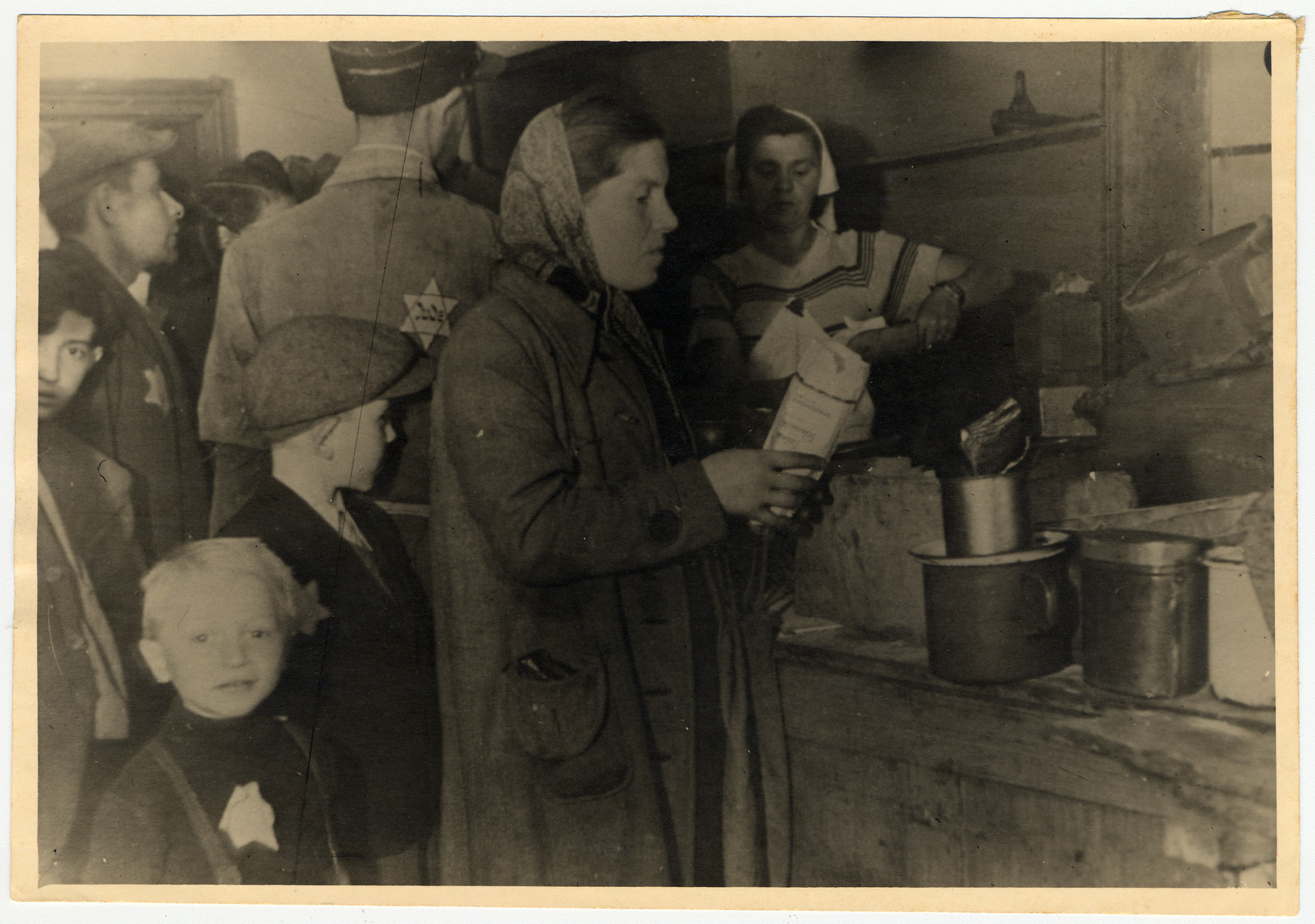 A woman and her child collect their rations at a food distribution center in the Lodz ghetto.   Photographer Mendel Grossman's sister and her son, Yankele, are in the foreground.