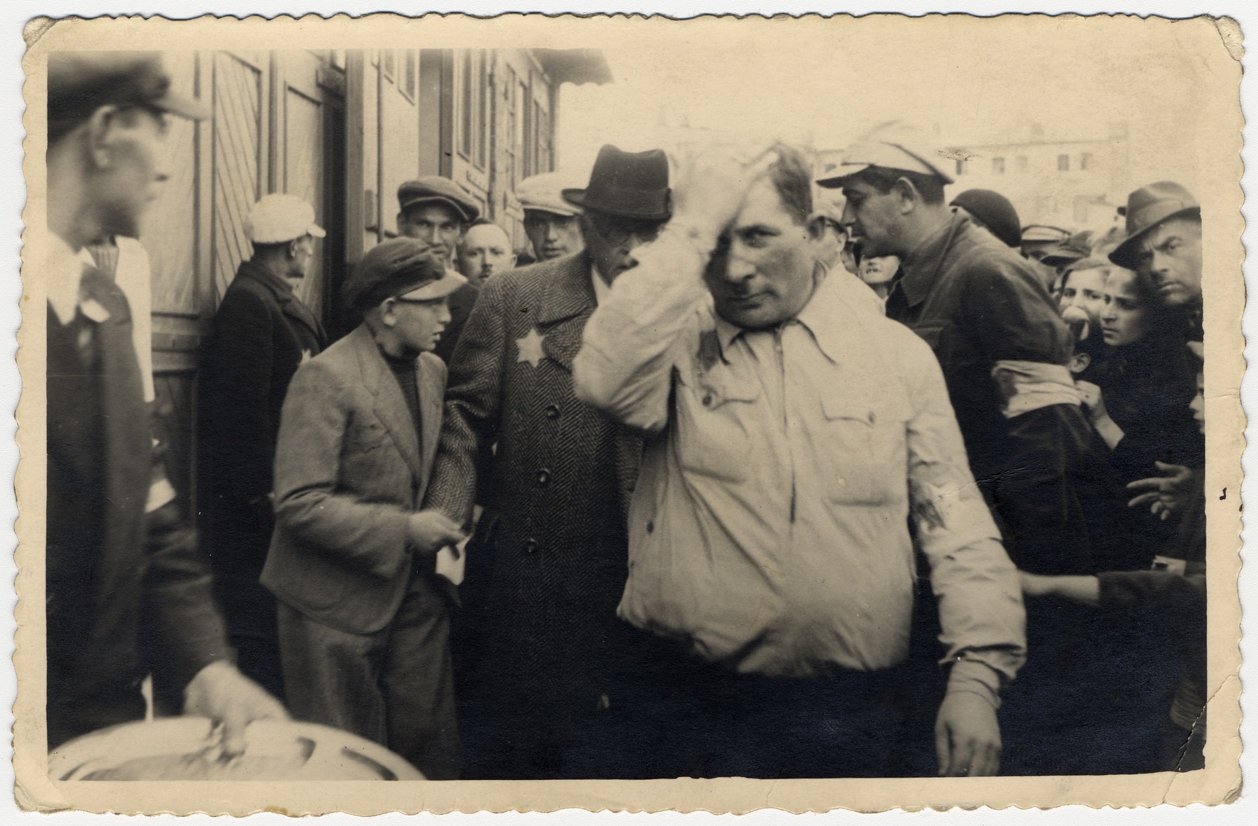 """A young man hands a petition to Mordechai Chaim Rumkowski surrounded by other ghetto residents.   The man in the foreground is Sergeant Kaufman.  The Yiddish inscription on the back reads: """"Sergeant Kaufman from the Jewish guard, here protecting the Chairman M.Ch. Rumkowski, who allowed a chosen child to approach him with a petition.  August 17, 1941"""""""