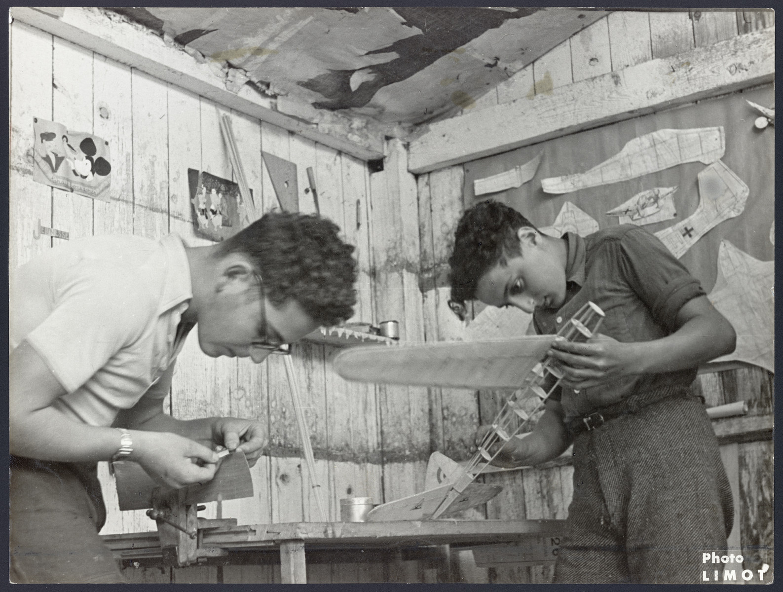Two teeange boys build wooden airplane models in a postwar OSE children's home in France.