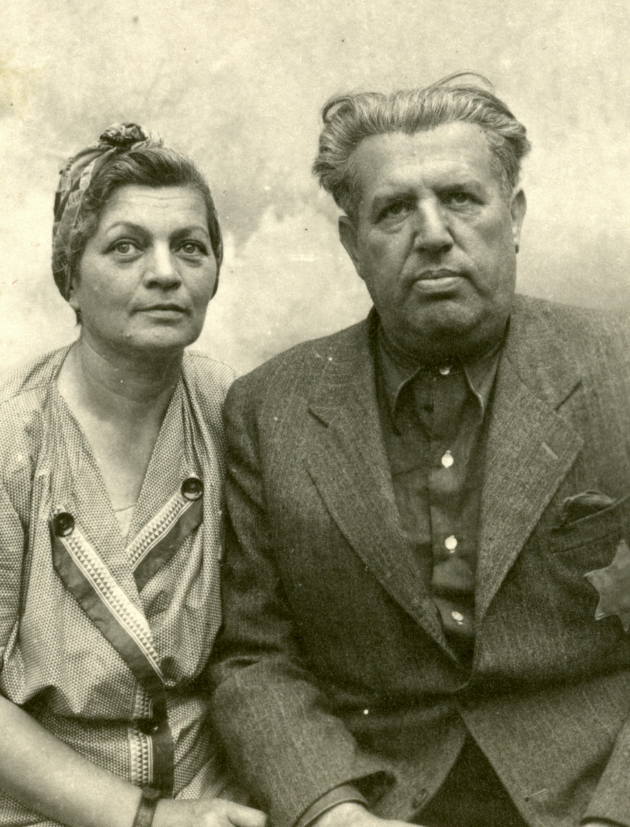 Gyula and Flora Breuer (Eli's aunt and uncle) sit for a studio portrait in Kolombus, Hungary.  They are wearing Star of David badges.