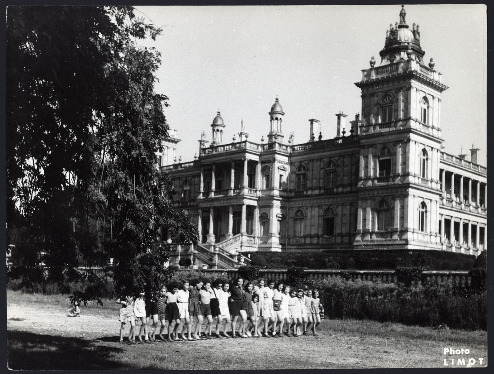 """Girls walk in a row on the grounds of the Rothschild castle.  The original caption reads """"Vacation at the Rothschild castle."""""""