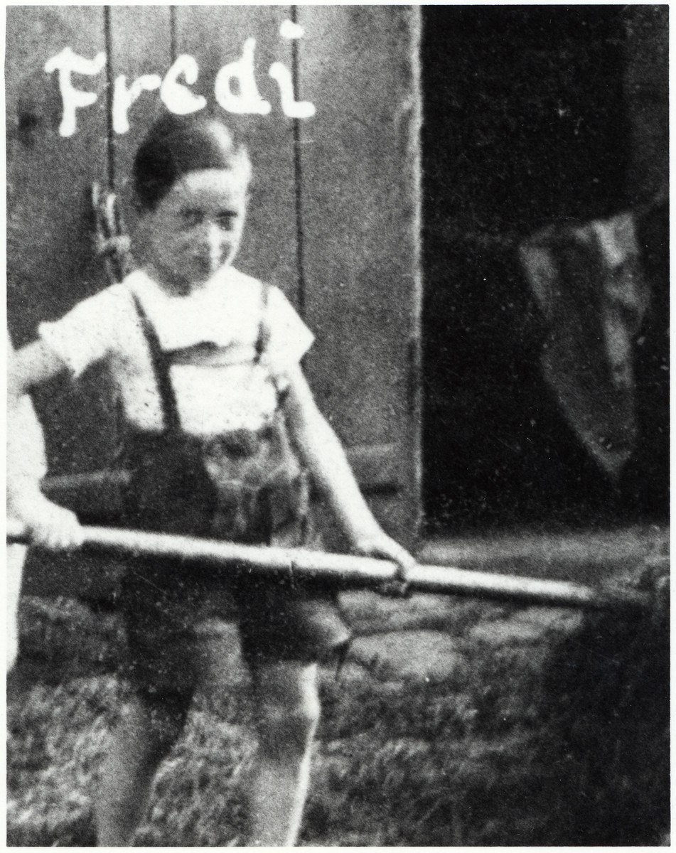 "Freddie Traum, an Austrian Jewish boy, pitches hay.  The original captions reads ""Me in happier times about 1937 making hay while the sun shines""."
