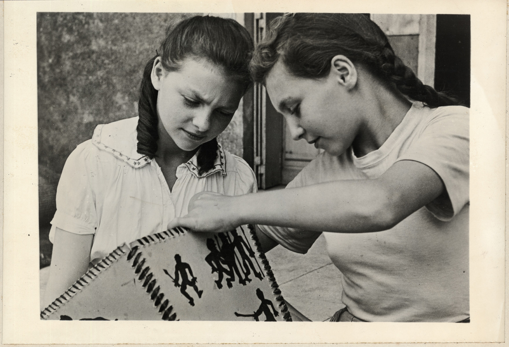 Two girls create a decorated lampshade in a postwar OSE children's home.