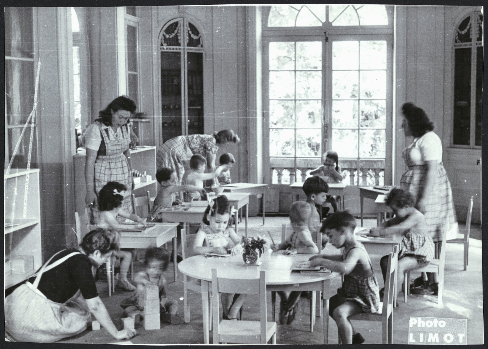 Young children, supervised by female staff, sit and play at tables in a classroom of a postwar OSE children's home.