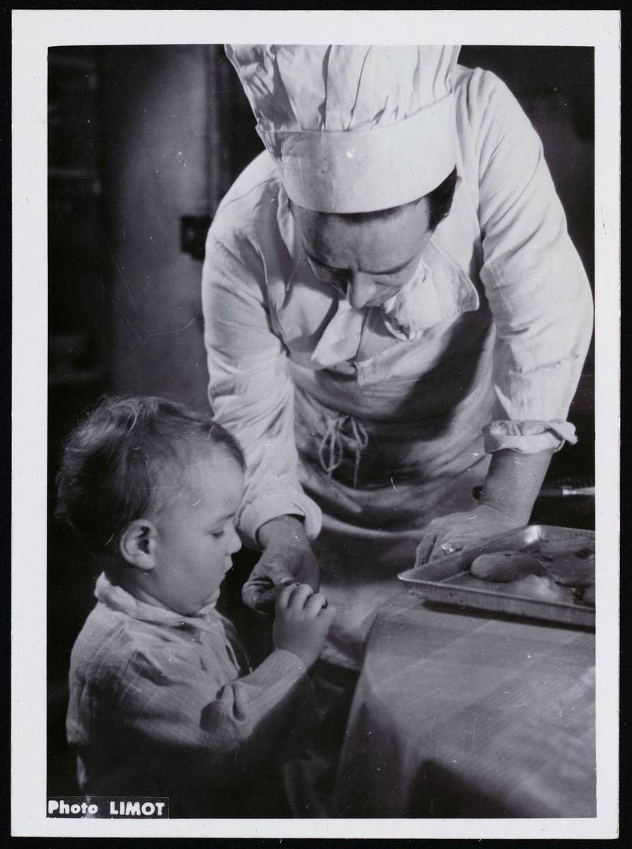 A chef gives a cookie to a toddler in a postwar OSE children's home.