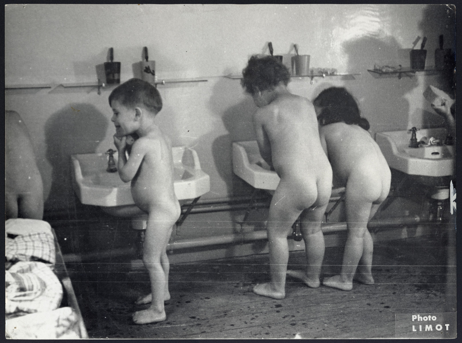 "Young children in an OSE/JDC children's home wash up and brush their teeth.  The original caption reads ""Its Fun to be Clean:  These French Jewish children who were hidden for years in caves and forests discover that running water and clean individual towels can be fun. These little ones who can scarcely remember home and family are now learning what decent living is like in a Joint Distribution Committee supported children's home near Paris.  Some 70,000 children receive J.D.C aid.  20,000 of them, for the most part orphans, are being cared for in 244 institutions which stretch from Brussels to Bucharest, from Paris to Prague.  In France alone there are 43 J.D.C. orphanages""."