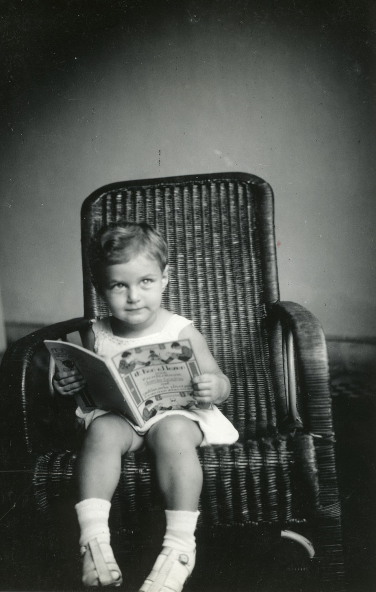 Chana Benninga sits in a wicker chair and reads a book while in exile in Indonesia.