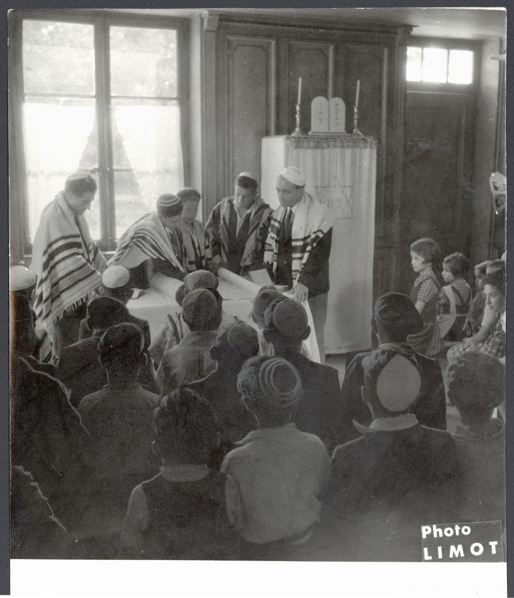 Young people read from the Torah in a religious service in a postwar OSE children's home.