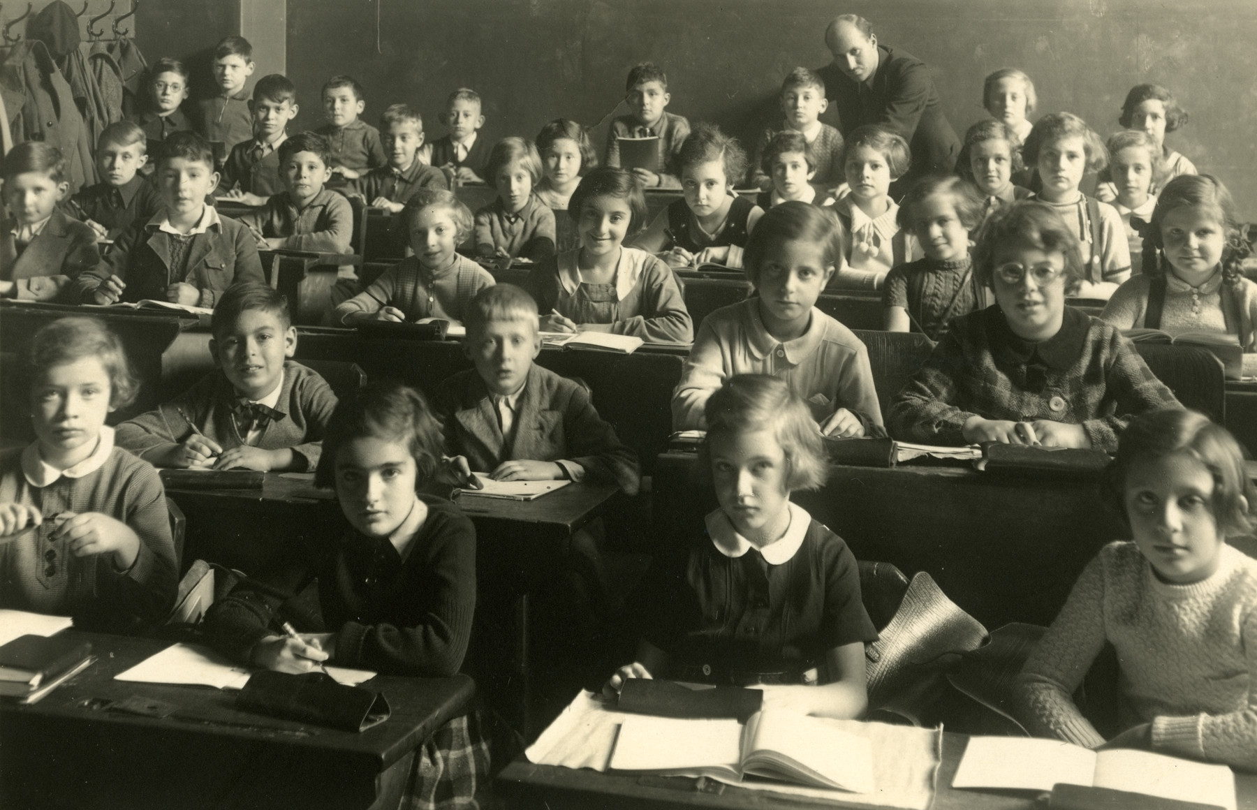 Children sit at their desks in the Carlebach School in Leipzig, Germany.  The donor, Irene Lewitt is seated in the second row, second from the right.  Pictured in the front row are Stephanie Bamberger (in the corner), Ruth Joskie (with white collar) and Miriam Hepner (to her left).  The teacher in the back is Felix Carlebach.