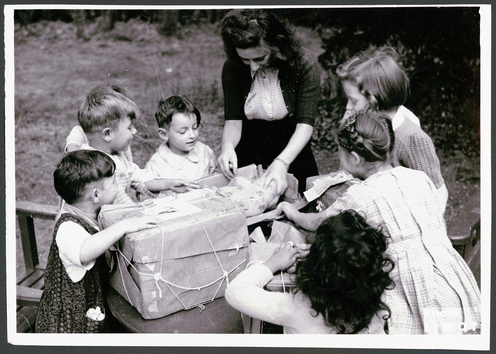 A female teacher helps young children assemble packages in a postwar OSE children's home.
