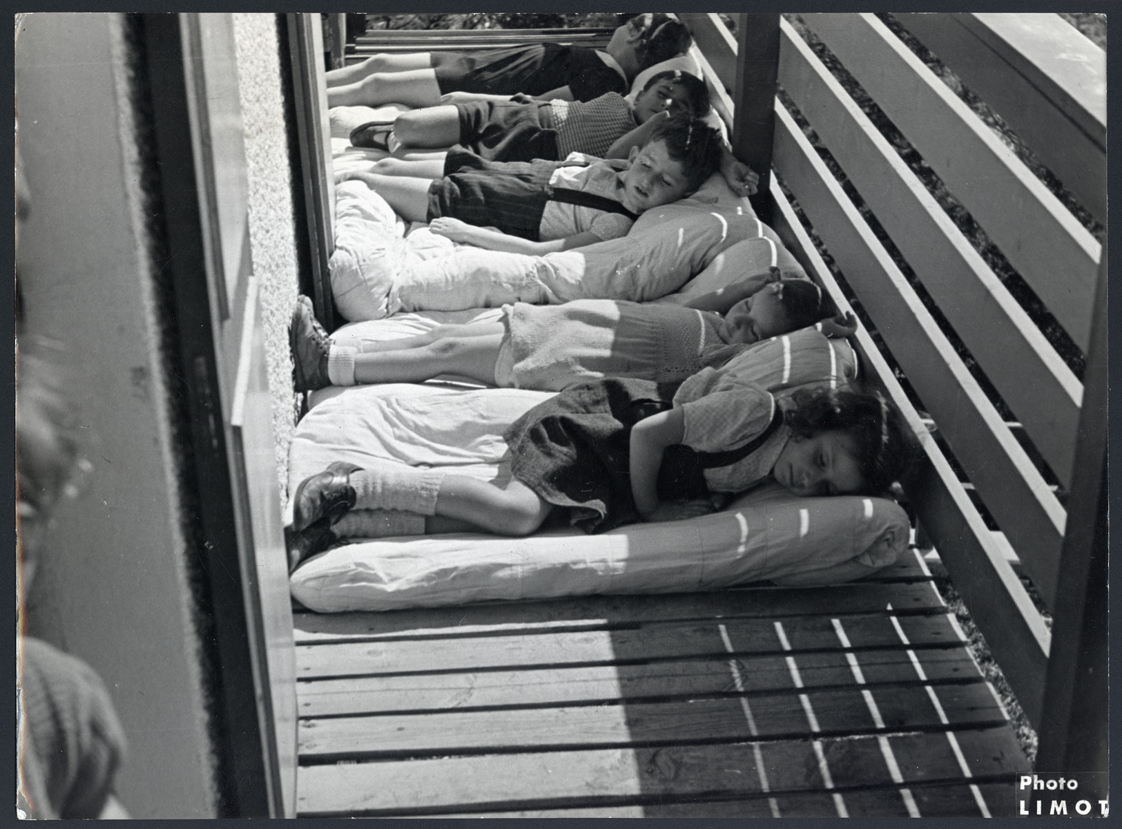 "Young children rest on a porch of a postwar OSE children's home.  The original caption reads ""It feels good in the sun."""