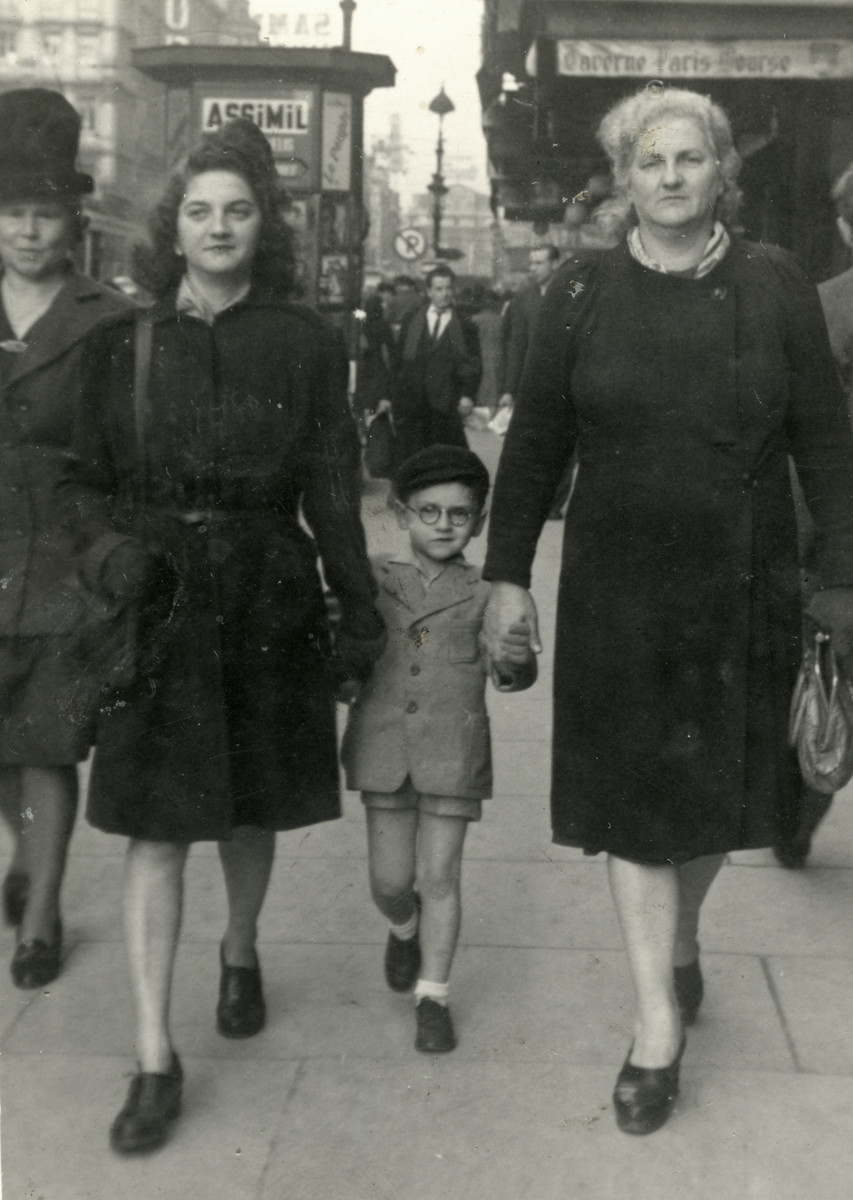 Claude walks down a street in Brussels after the war with his older sister Renee (left) and mother (right).
