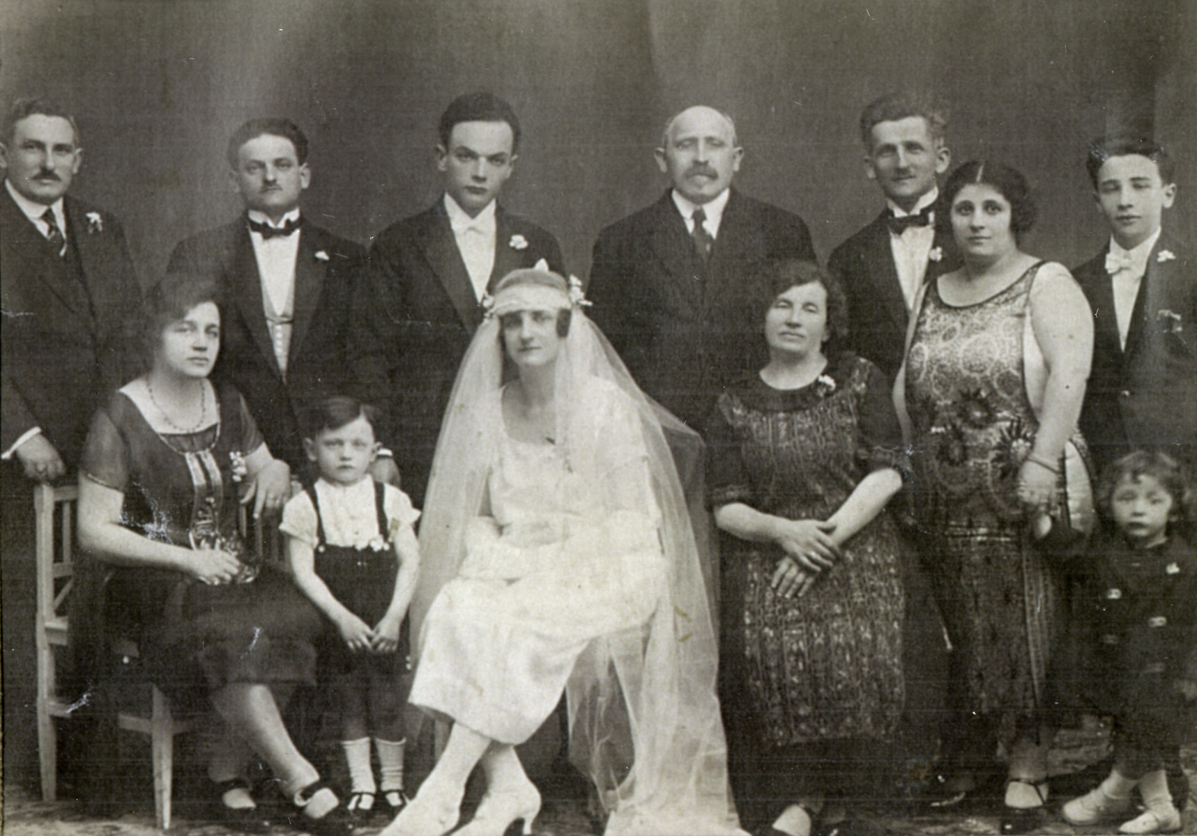 Wedding of Natan Zeidenbach and Mathilda Herscovici.  Back row: Teichberg (far left) survived, Bernard Herscovici (3rd from the right) perished in Auschwitz, Max Herscovici (2nd from the right) survived and after the  war established himself in Brussels with his wife, Anoutsa Grimberg.    Front row: Shimon Herscovici (2nd from the left) worked two years in the revier in Auschwitz. He was a medical student.  Chava Herscovici (right of the bride, sitting) perished in Auschwitz with her husband Bernard (standing at her left shoulder), Anutsa Greenberg Herscovici (2nd from the right) survived.