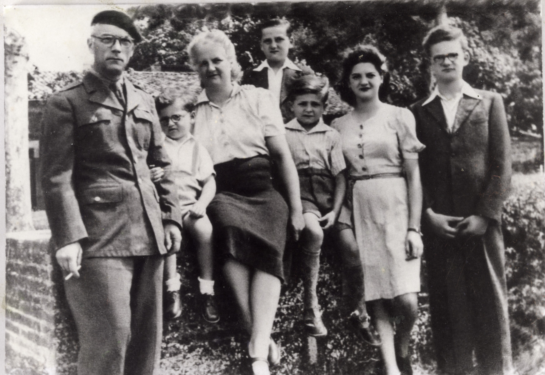 Five children reunite with parents after the war.  Father is wearing a resistance Macquis uniform.