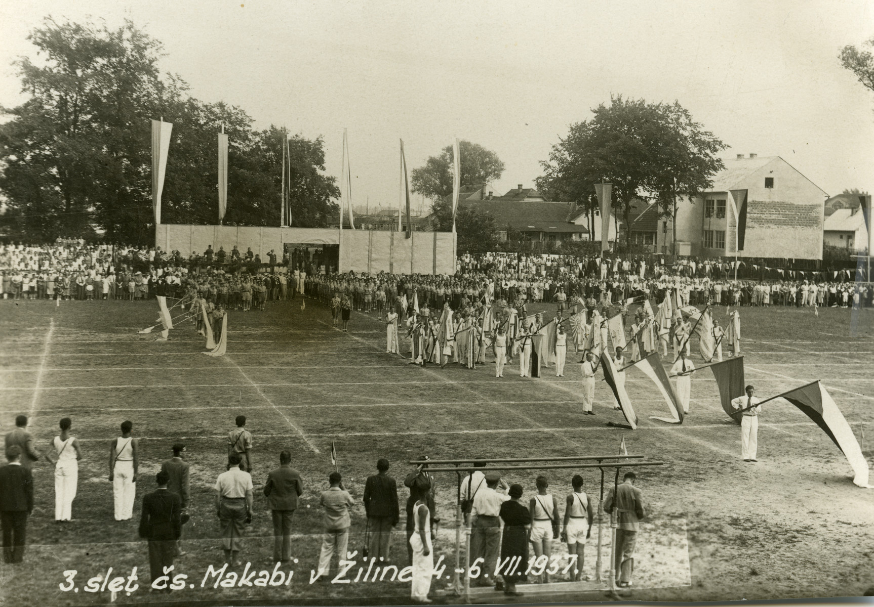 Members of the Zilina Maccabi gymnastics team stand in formation holding flags on a sports field.