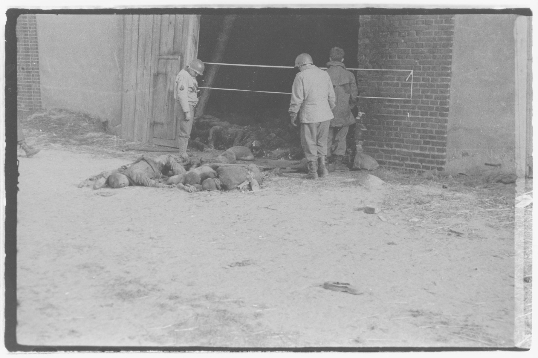 US Army officers from the 91st Evacuation Hospital Unit investigate the aftermath of the Gardelegen Atrocity.