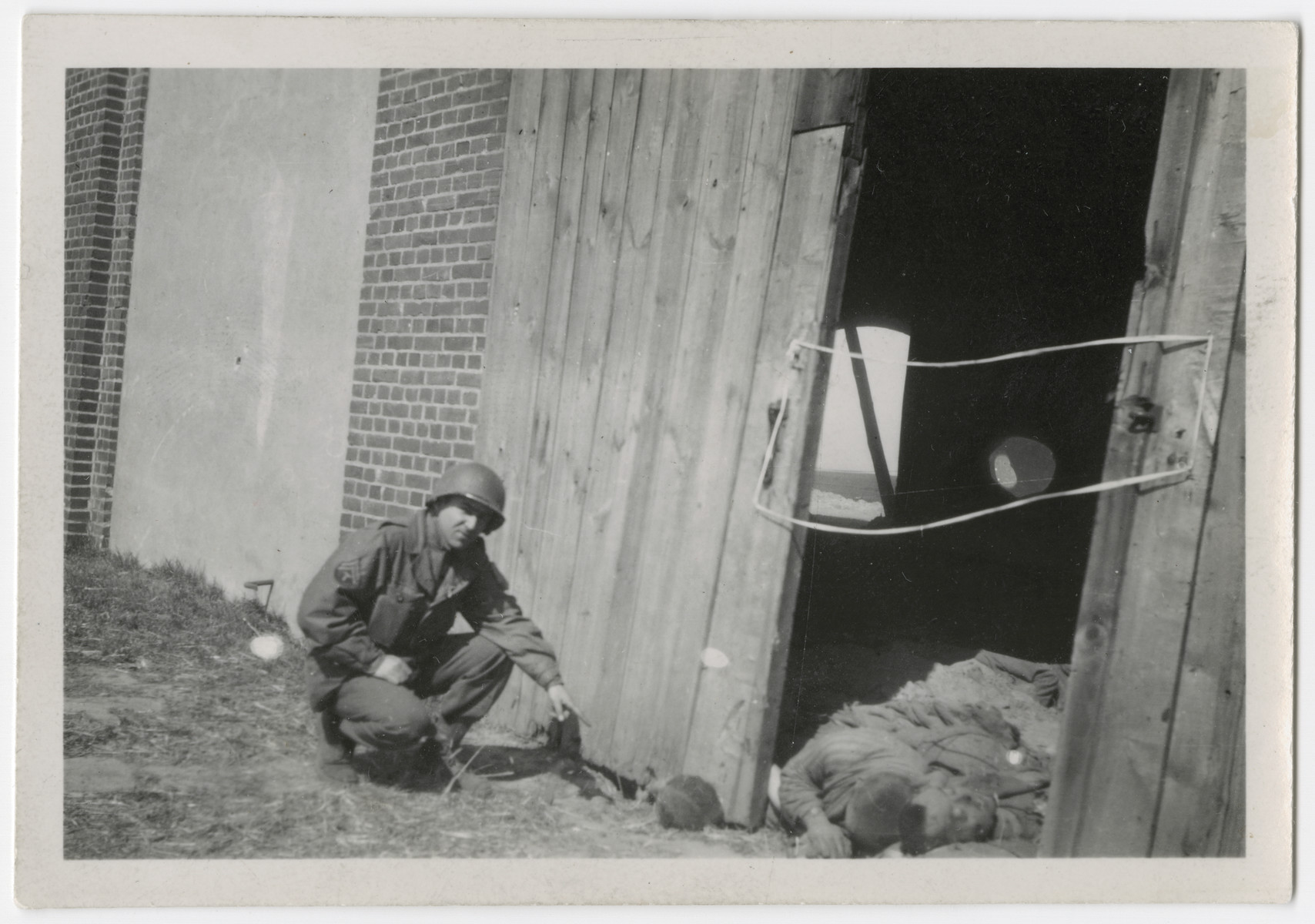 US Army Officer John Shaheen points to corpses in the barn at the Gardelegen Massacre.
