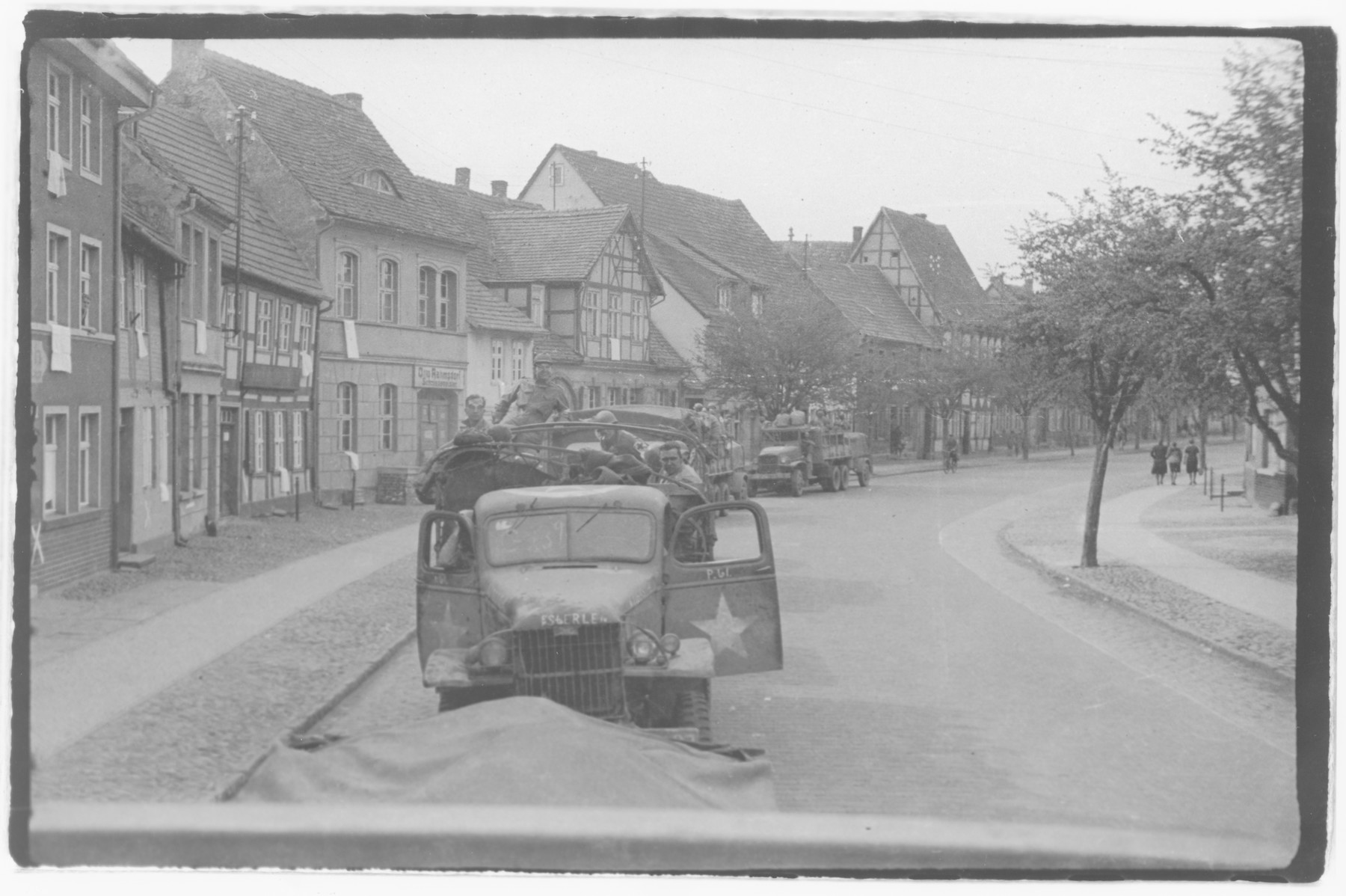 US Army officers from the 91st Evacuation Hospital Unit drive through a German town.