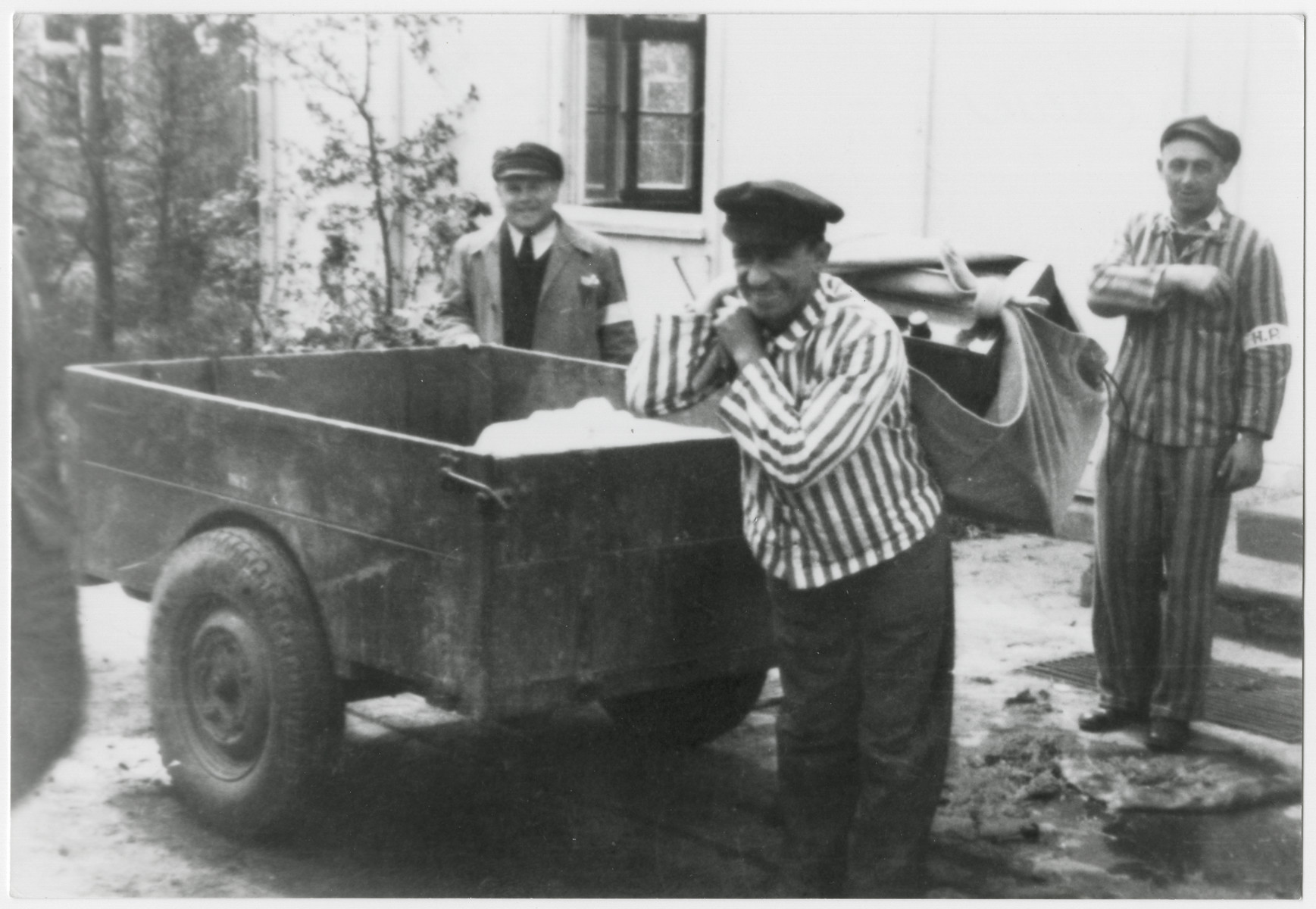Survivors of the Dachau concentration camp haul electrical equipment in a sack.