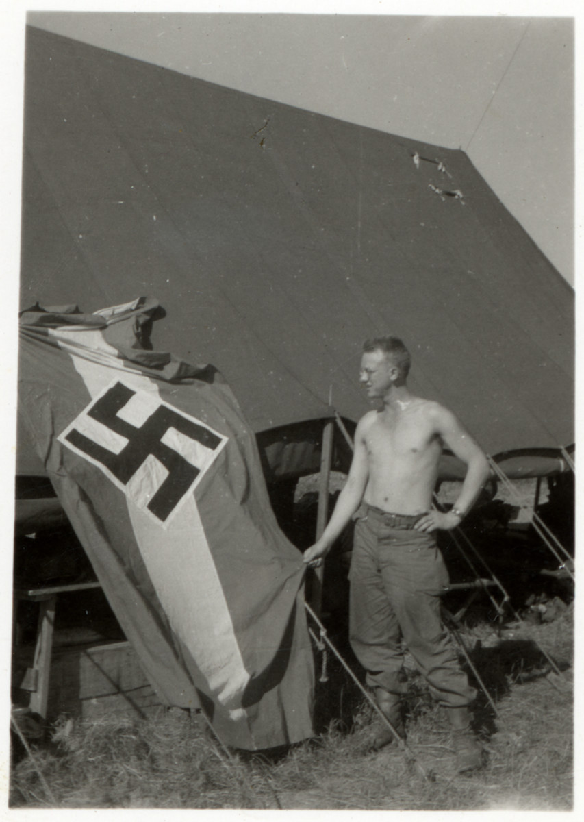 Lloyd Rissinger, a liberator of the Ohrdruf concentration camp, poses next to his tent and and a captured Nazi flag.