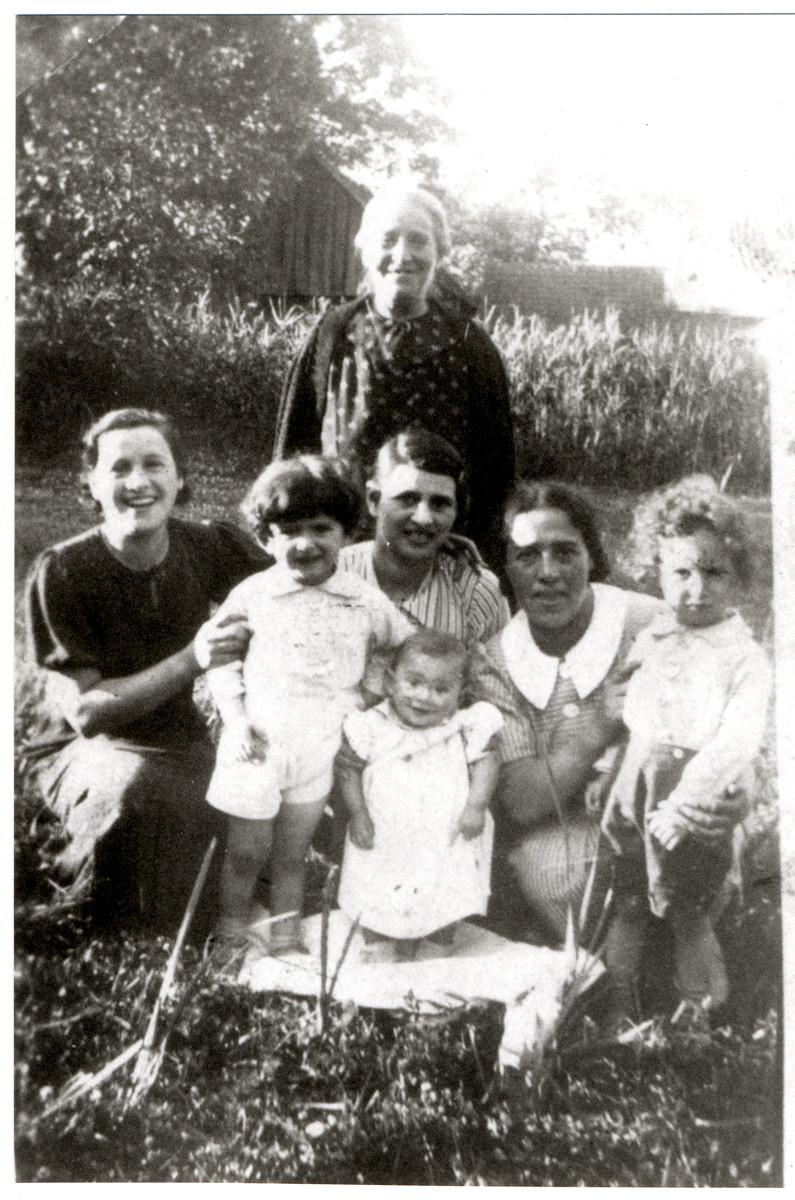The Rosenbaum family poses on a lawn in prewar Drohiczyn.   Standing in the back is Chana Malka Perkovitsky Rosenbaum.  Squatting are Zlata Riva Rosenbaum (Grynblatt), Mrs. Menachem  Rosenbaum and Gurah Lesah Rosenbaum Taumschen. The children from left to right are Yosef Rosenbaum, Henye (daughter of Menachem), and Yakov Leib Taumtschen.