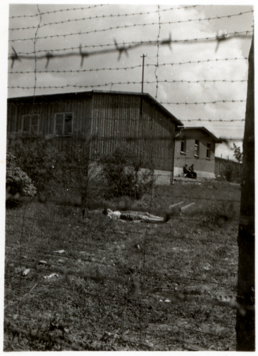 View taken from behind a barbed wire fence of a survivor or victim lying on the ground outside a barrack in the Ohrdruf concentration camp.