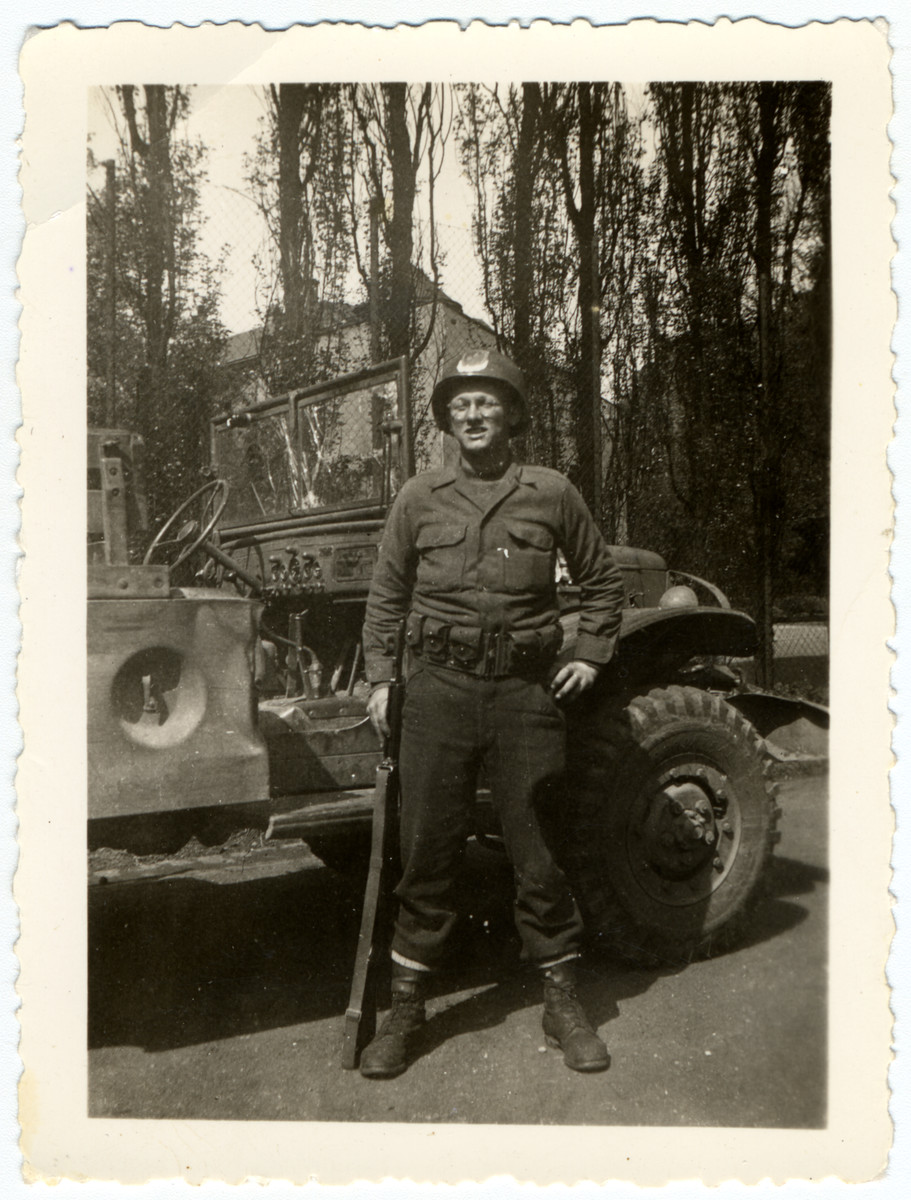 Lloyd Rissinger, a lliberator of the Ohrdruf concentration camp, poses next to his jeep.