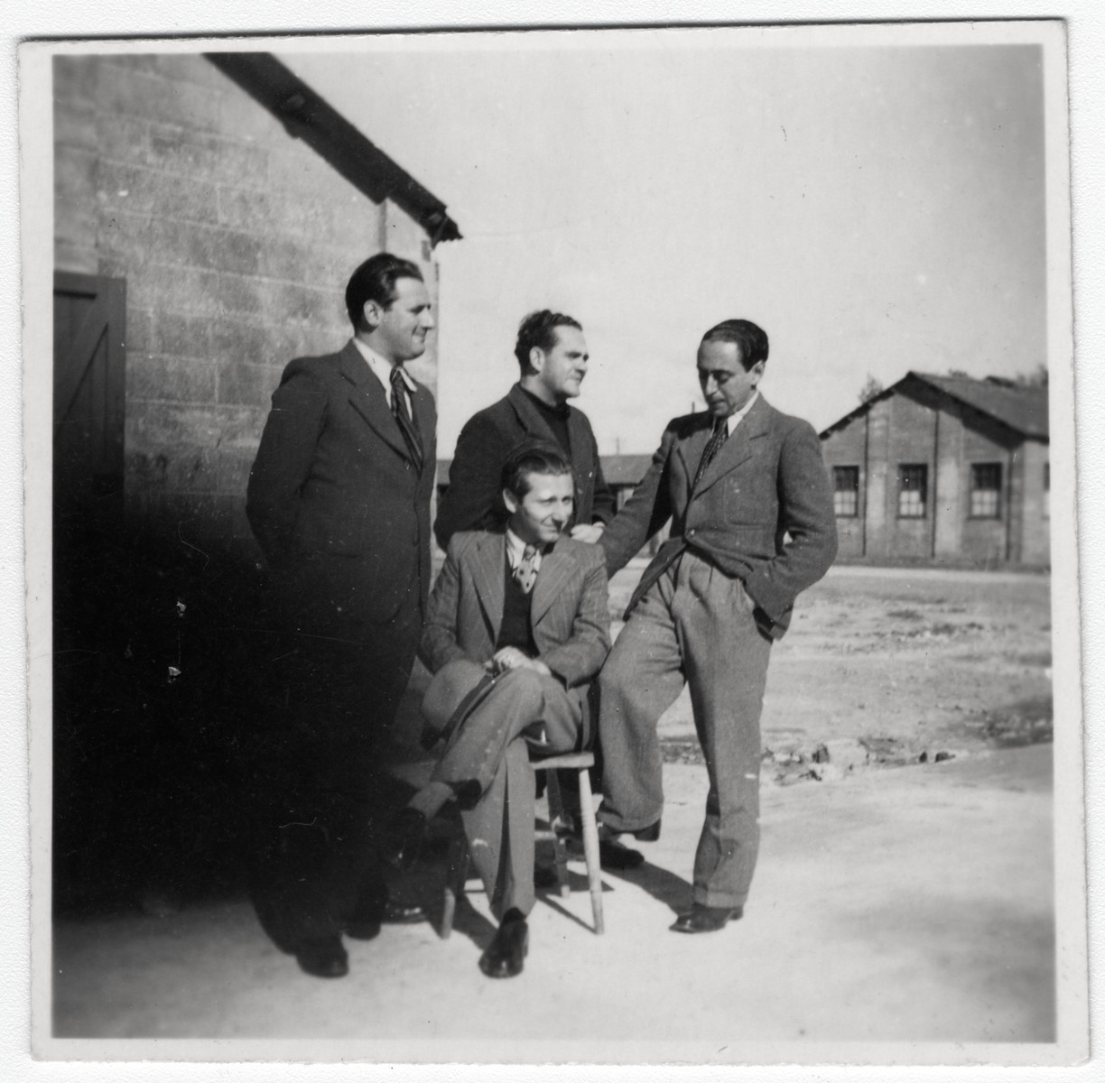 Portrait of four German or Austrian Jewish refugees posing outdoors in the Kitchener refugee camp.
