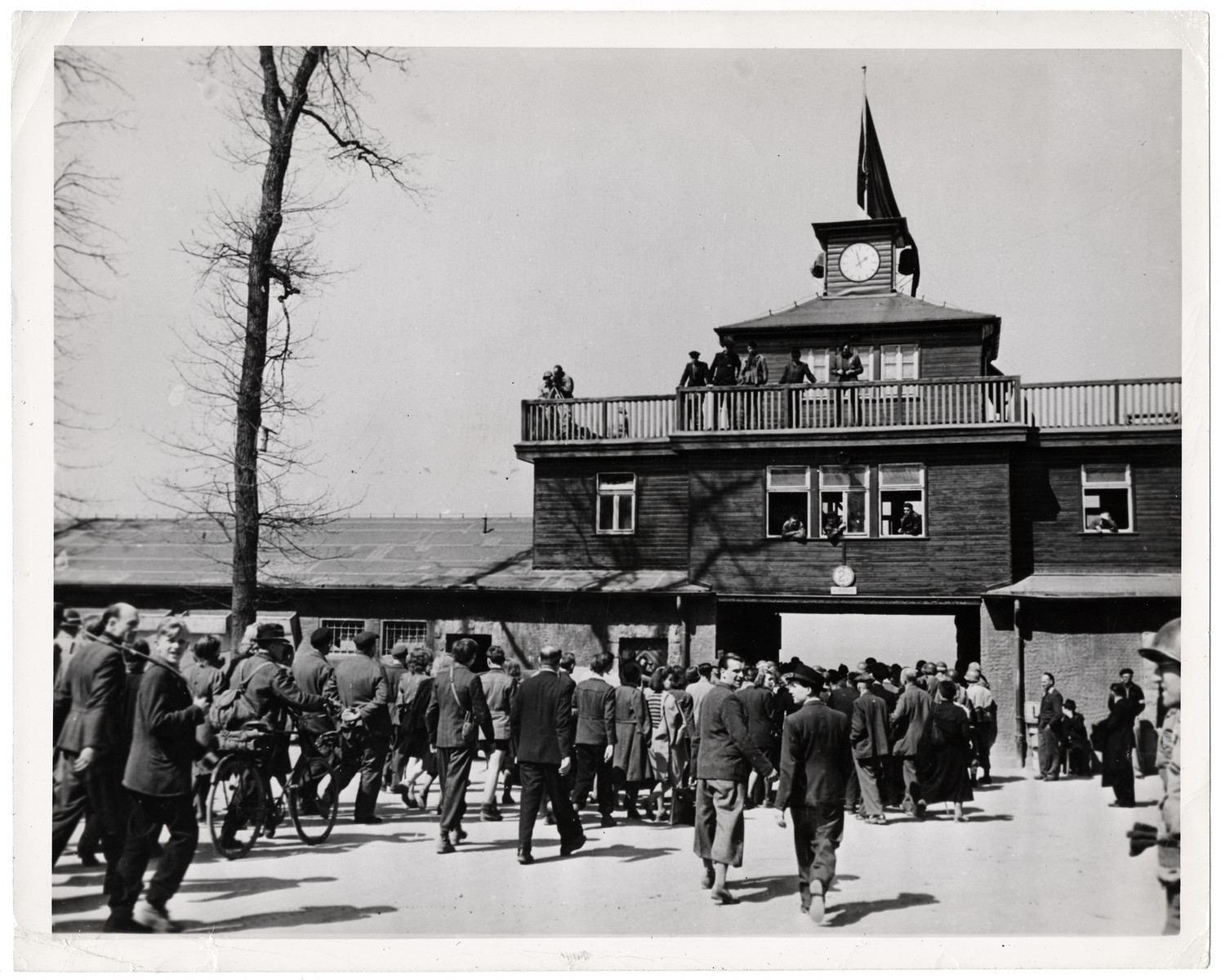"Original caption: ""German civilians, selected from all walks of life in nearby Weimar, are marched into Camp Buchenwald. Escorted by military policemmen of the Third U.S. Army, the civilians were forced to witness all the evidence of Nazi atrocities in the camp. The black flag atop the tower was hung because of President Roosevelt's death.   The Buchenwald concentration camp, on a small hill about four miles outside Weimar, was captured April 13, 1945, by troops of the Third U.S. Army. Approximately 21,000 inmates ---- Russian, Polish, French, Italian and Czechoslovakian --- were liberated. They were the living dead. Some clustered weakly about the first Americans to enter the camp and died as they spoke. Children had convict numbers tattooed on the stick-like arms. In 10 years, more than 70,000 persons were starved and butchered in this camp. Nazi scientists had a field of death to pick from at Buchenwald for their experiments. A crematorium was operated until the German ran out of coal, then the bodies were stacked up in two rows like cordwood. One of the barracks where prisoners were quartered until they died had once stabled 80 horses. The Germans put 1,200 men in it, five to bunk. Every 24 hours, prisoners received a small piece of brown bread, a little margerine and one scant portion of stew."""