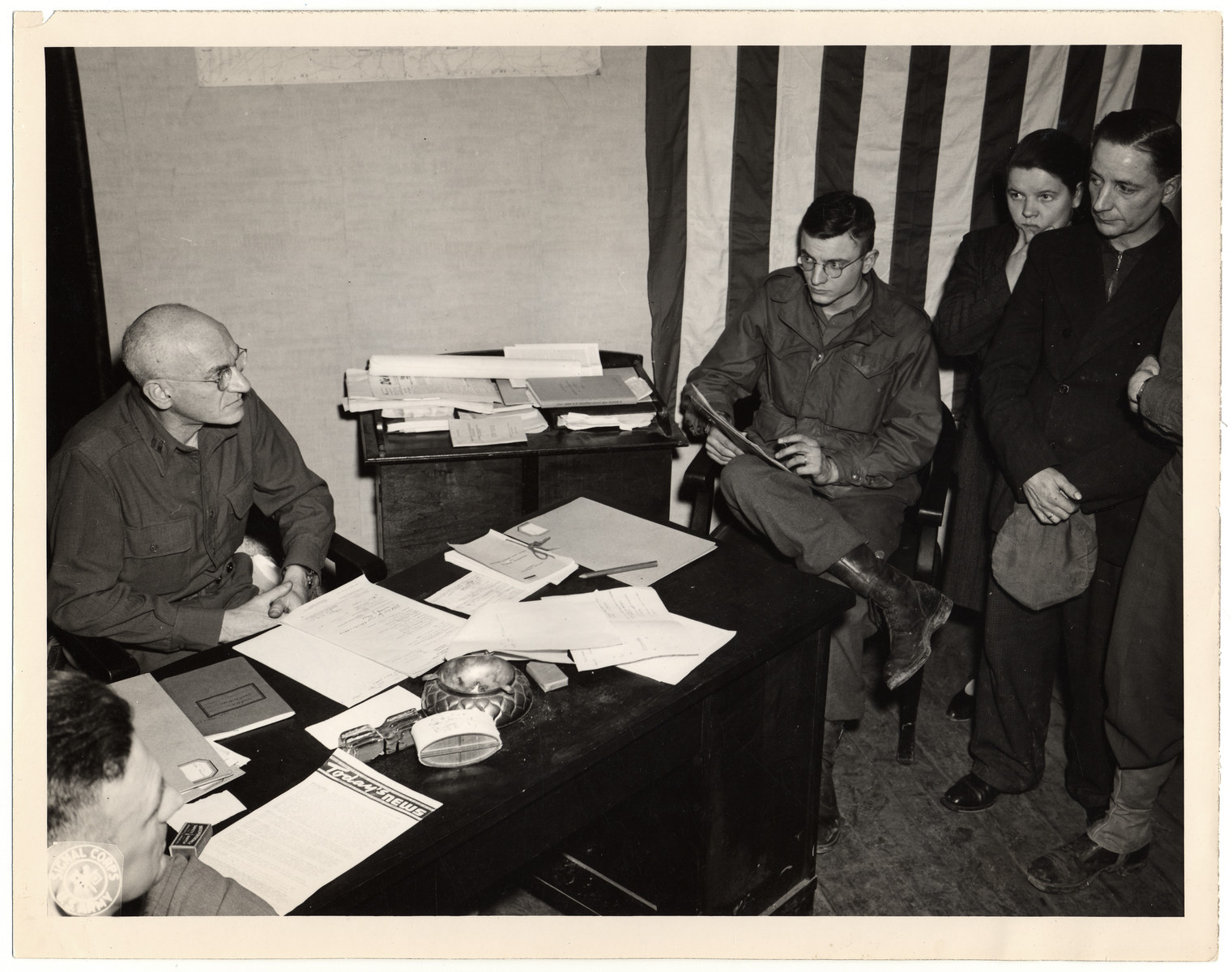 "An American judge oversees the trial of German civilians accused of looting.  Original Caption: ""Court-martial of two civilians accused of looting. From left to right: Capt. Lewis Tyroler judge, the court reporter and the two accused."""