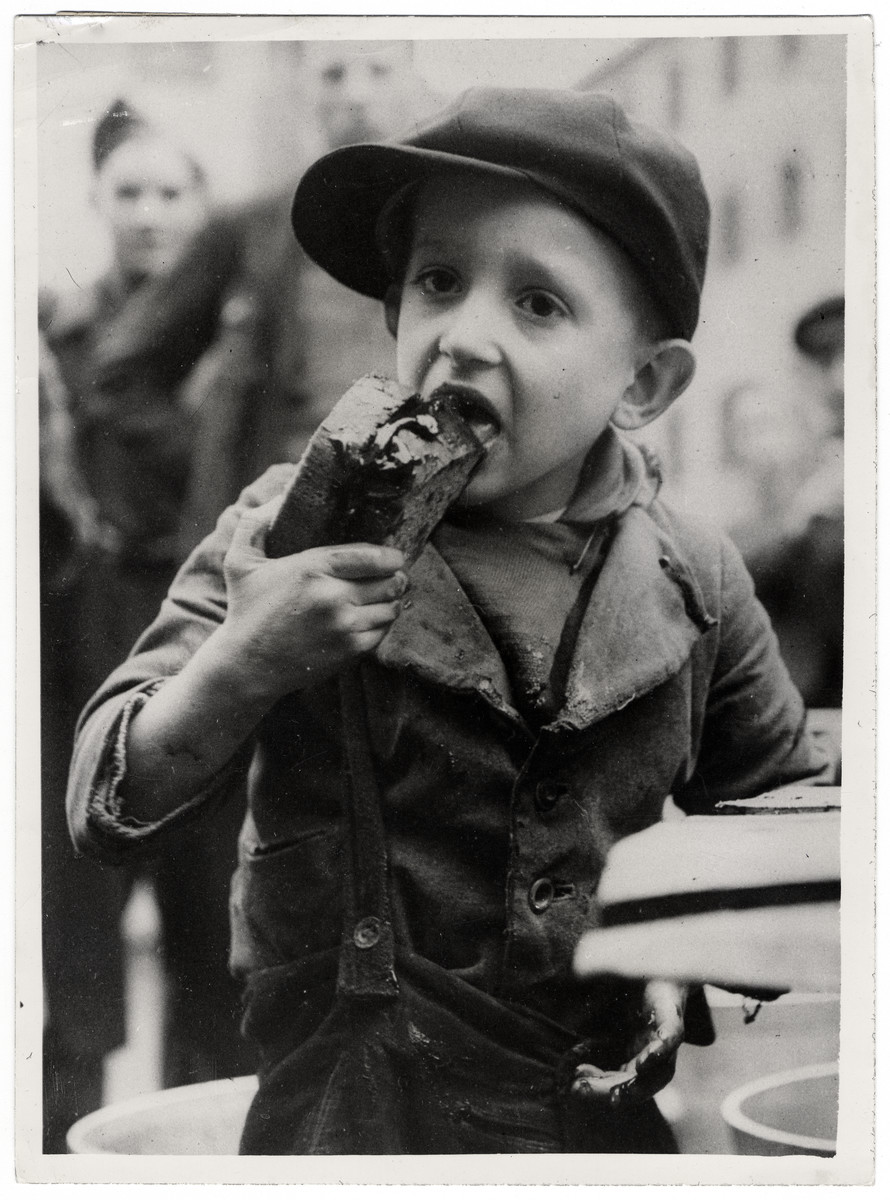 "Original Caption: ""A Russian youngster eats hungrilly of bread and molasses. Men, women and children of all ages are walking into free air from their cells in the wake of Allied spearheads.  As Allied armies on the Western front sweep eastward across the Reich, they are freeing tens of thousands of foreign workers from Nazi slave labor camps. These displaced persons are tempoarily places in repatriation camps until they can be transported to their homelands by the Allies. At the camps, they are carefully questioned to make sure they are not German soldiers disguised as civilians. At one displaced persons center, 28 out of 3,000 men proved to be German troops attempting to flee into Belgium and Holland.  By March 19, 1945, freed French slave workers were arriving in Paris at the rate of 2,000 daily and it was estimated that approximately 2,500,000 French nationals were still inside Germany. Estimates of the total number of foreign workers in the Reich run as high as 20,000,000, most of them being Russians or Poles. U.S. General of the Army Dwight D. Eisenhower, Supreme Commander-in-Cheif Allied Expoditionary Force has requested the United Nations relief and Rehibilitation Administration to train between 3,500 and 6,000 persons to operate assembly centers, and 21 UNRRA teams had arrived in Europe by March 31.  These pictures show a few of the 5,000 displaced persons registered at a single repatiation camp on the Western Front during 12 days. """