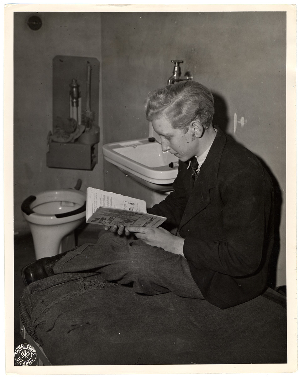 "A former member of the  Hitler Youth sits in prison for a curfew violation.  Original Caption: ""Hermann Vosinsky 15 years of age who was a member of the Hitler youth organization. He was arrested in Aachen after curfew hours. His sentence was 6 months, but all suspended but 15 day. If caught again he shall serve 6 months without trial."""