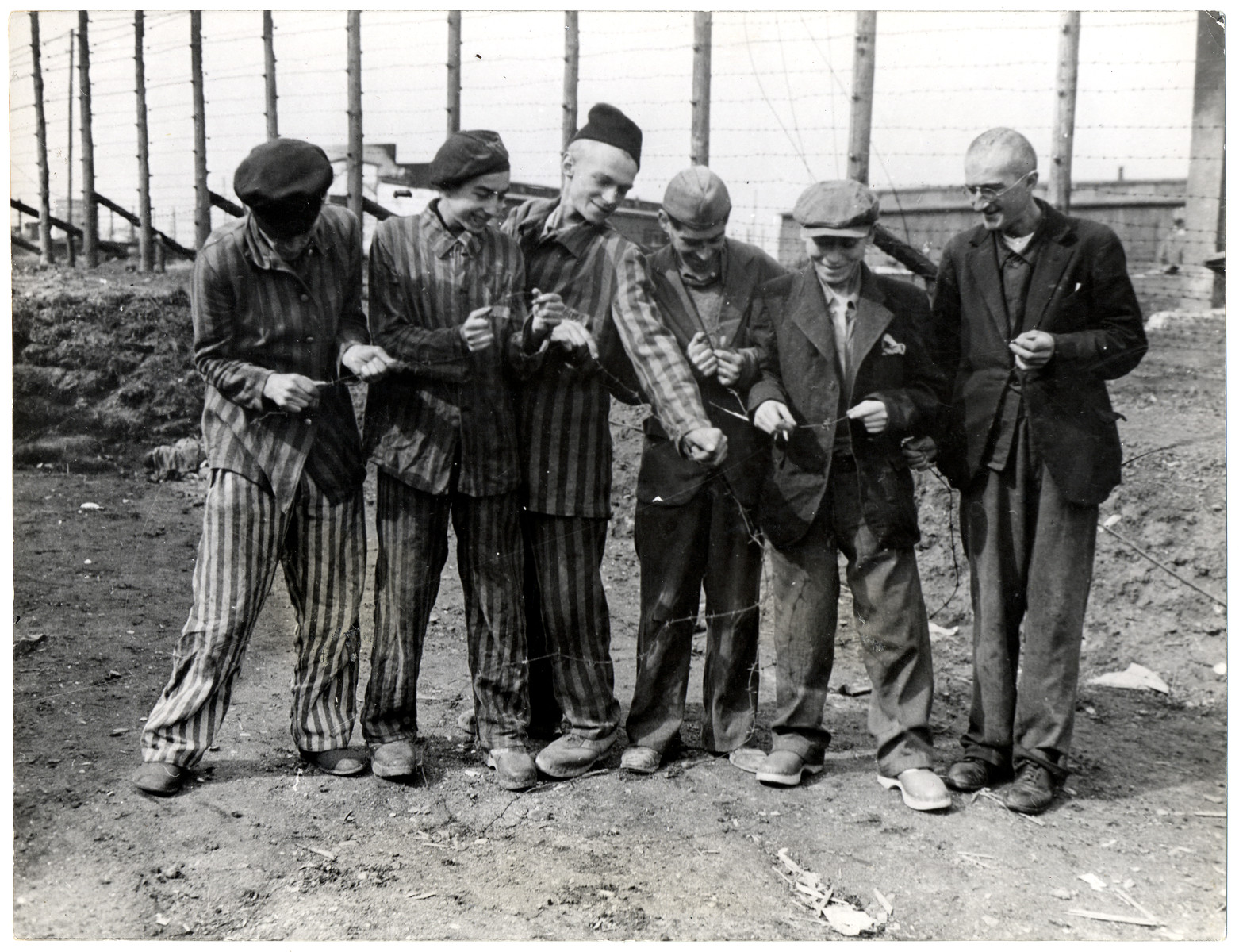 "Survivors of the Hanover concentration camp destroy the barbed wire that had held them captive.  Original caption reads; ""Former Jewish and Polish prisoners of the Nazis laugh at the barbed wire which for years held them captive at the Nazi Hanover-Harlen concentration camp near Hanover, Germany, captured by troops of the Ninth U.S. Army April 10, 1945. Hanover is 155 miles from Berlin."""