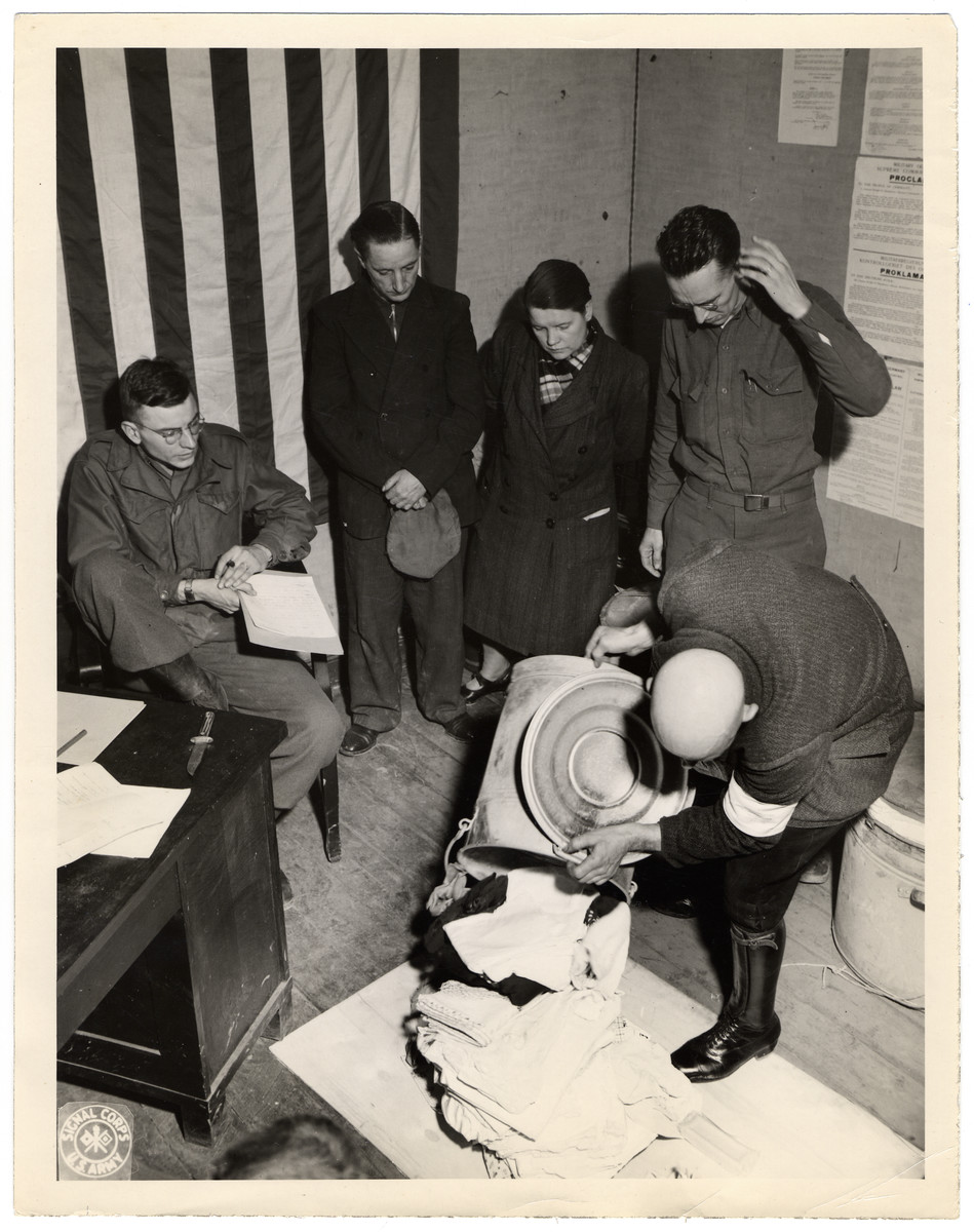 "American soldiers oversee a court-martial of German civilians accused of looting.  Original Caption: ""Court-martial trial of two German civilians accused of looting property from an abandoned and severely damaged house in Wuerselen. A civilian auxiliary policeman in exhibiting the property to the court. From left to right- the recorder, the two accused and the interpreter, then the civillian policeman."""