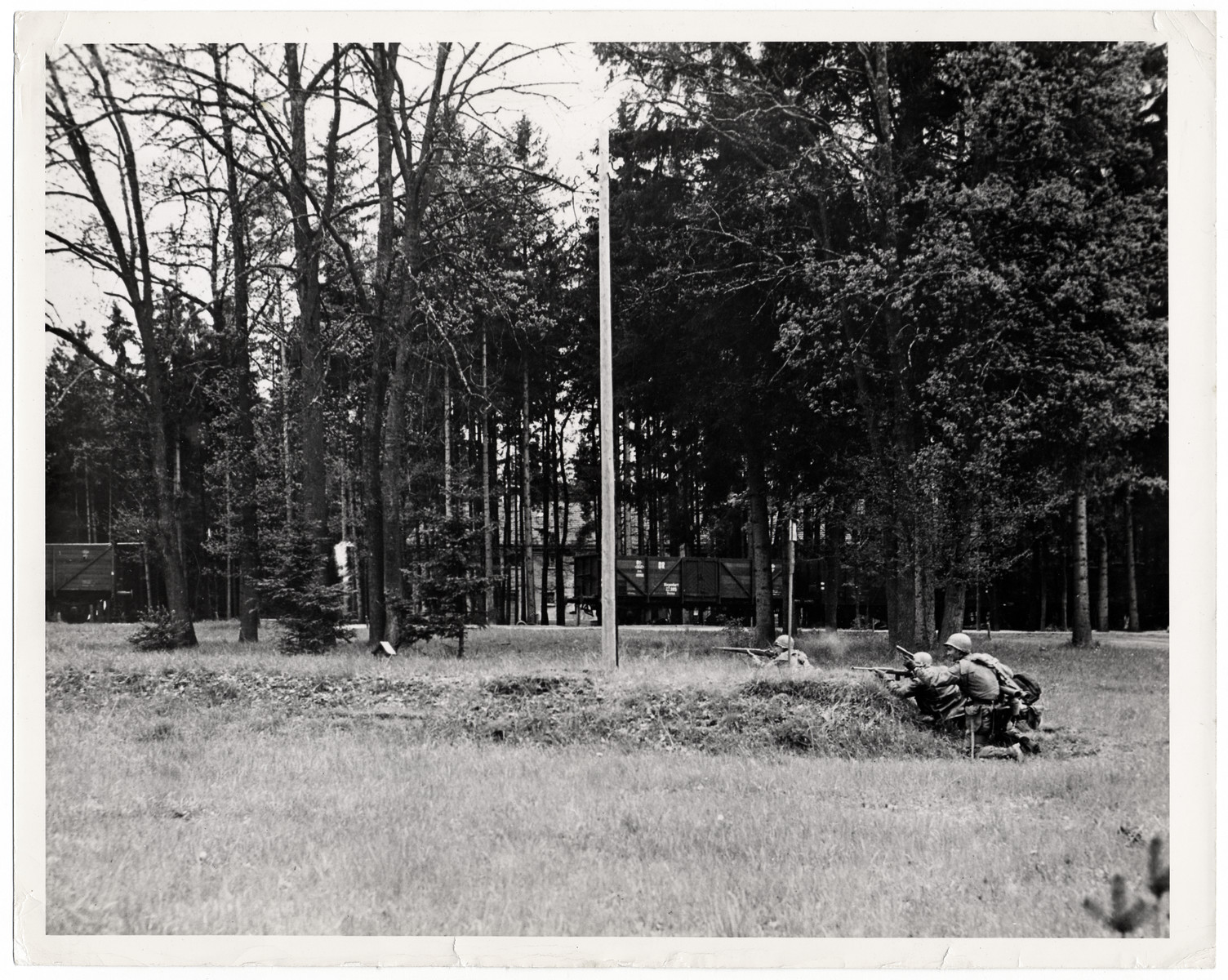 """Original Caption: """"Seventh U.S. Army tankmen use a small knoll in Dachau to fire at fleeing SS guards as they liberated the infamous torture camp.  Horrors worse than those found in the German concentrations camps of Buchenwald and Belsen were discovered in the stinking hell-hole of Dachau, captured by troops pf the 42nd and 45th Infantry Divions of the Seventh U.S. Army April 30, 1945. More than 32,000 prisoners were liberated, among them some Englishmen, Canadians and Americans. The camp was formally surrendered by an SS Lieutenant carrying a white flag, accompanied by a Swiss Red Cross official, but SS troops opened fire as American troops approached the entrance. The Germans were shot down. Three prisoners were electrocuted when they tried to burst throught the electrified barrier to welcome the Americans. SS guards opened fire on other prisoners who went wild with joy and rushed to meet the liberating troops.  Prisoners with access to records said 9,000 people died of hunger, disease or shooting within the past three months at Dachau. Four thousand more perished during cold winter months. When Americans entered the camp, they found 50 open railway cars standing on a siding, apparently full of oiled, dirty clothing but actually found hundreds of corpses piled on top of each other. They also found a row of kennels where fierce dogs were kept to set after escaping men. They discovered gas extermination chambers, incinerators full of naked bodies, bodies marked for dissection and bodies of several small children.""""    This Photo Shows: """""""""""