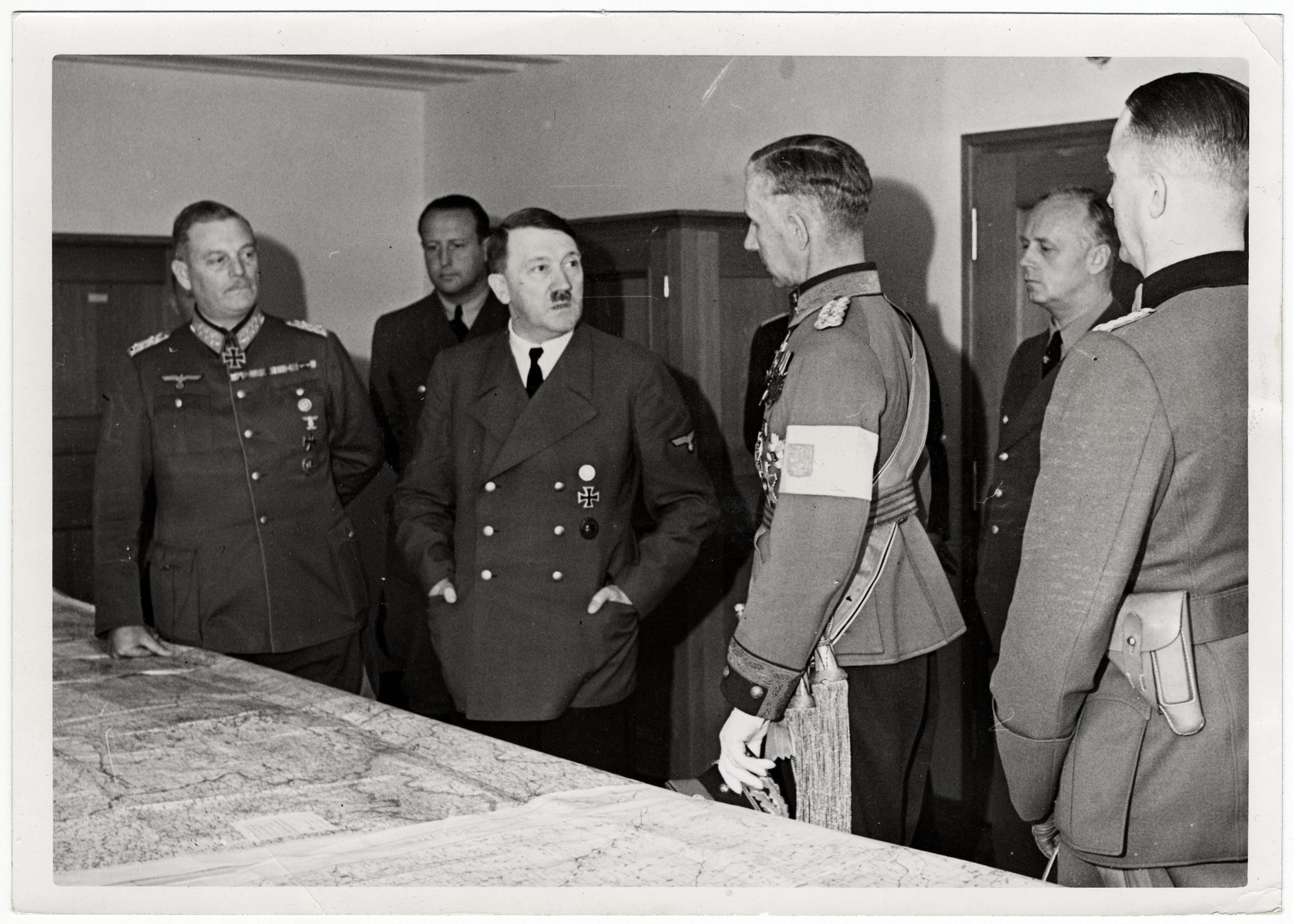 Adolf Hitler meets with several of his key military advisors in the map room of his headquarters.  Pictured with Hitler are General Wilhelm Keitel, Lieutenant General Harald Oehquvist, Joachim von Ribbentrop and General Gerhard Matzky.