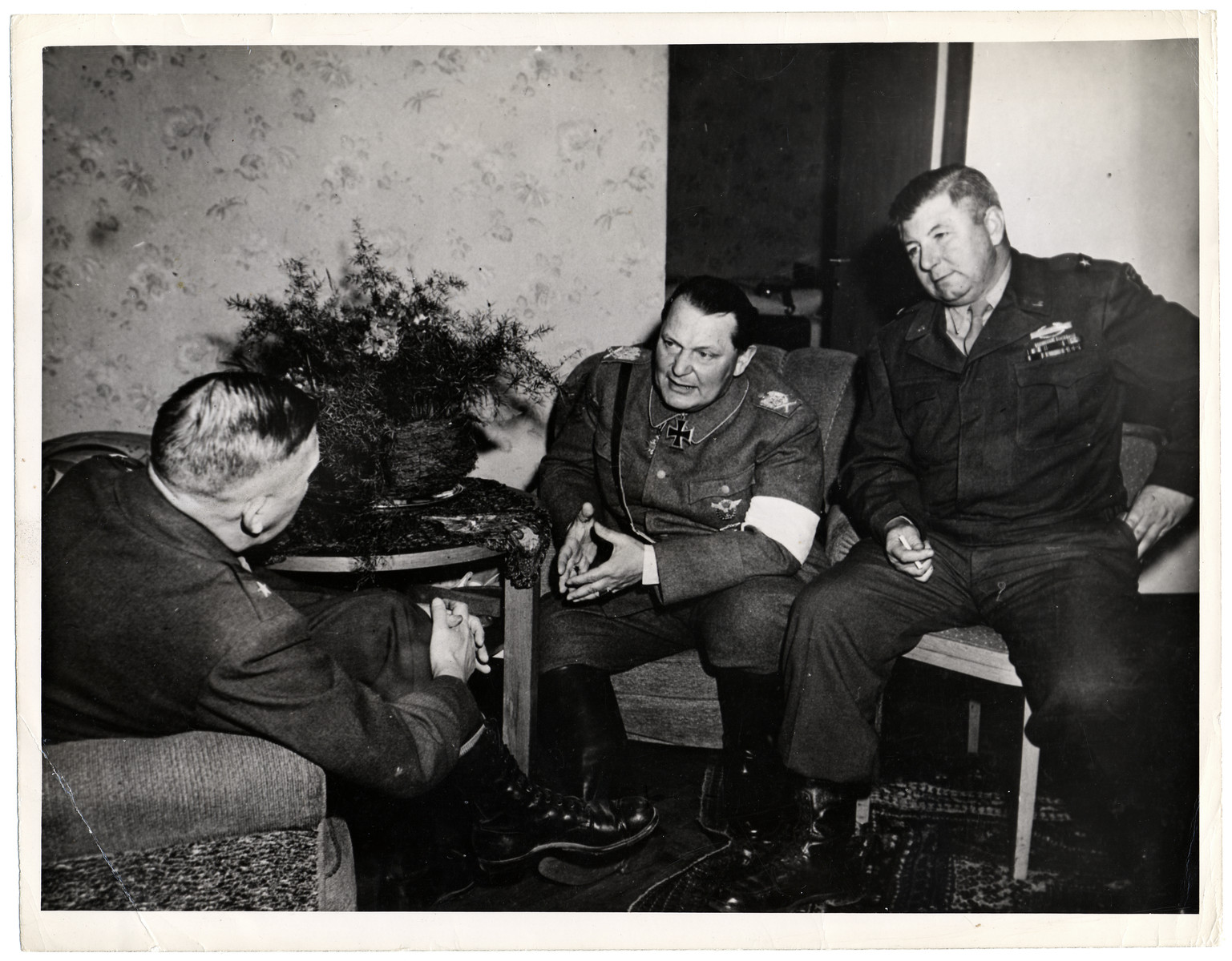 "Hermann Goering (center) talks with Brigadier General Robert J. Stack, Assistant Commander of the 36th Infantry Division (right) and Major General John Dahlquist, Commander of the 36th Division after his arrest in the Grand Hotel at Kitzbuehl.  Original Caption: ""Herman Goering, second to Adolf Hitler in the Nazi Party hierarchy, was captured by troops of the 36th Divion, Seventh U.S. Army, at Kitzbuehl, Austria, it was announced May 9, 1945, by Supreme Headquarters Allied Expoditionary Force. He surrendered to Brigadier Gerneral Robert J Stack, Assistant Commander of the 36th Divion. Goering said that the last time he spoke to Hitler was April 24, 1945, when he said he telephoned the Fuhrer and suggested that he assume command as Germany was being cut in two. Goering claimed that Hitler had become outraged, accused him of losing faith and said that the death sentence would be passed."""