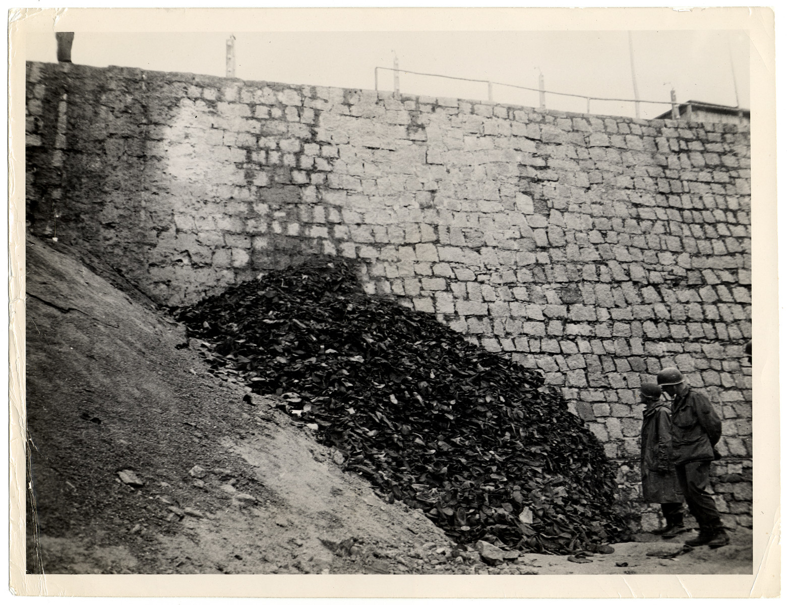 """US soldiers examine a pile of shoes that had belonged to prisoners stacked against a wall in the Flossenbuerg concentration camp.  Original caption reads: """"When troops of the 90th Infantry division, Third U.S. Army, captured Floss, Germany, six miles from the Czechoslovakian border, another Nazi concentration camp passed out of existence. The camp, fenced off with electrical barbed wire, contained 16,000 sick and starved inmates, including 400 cases of typhus. Originally, the enclosure confined 60,000 political prisoners and military prisoners-of-war of all nations. It was estimated that 1,400 a month died of starvation after which their remains were burned by Nazi guards. Before the Germans fled ro rear areas all inmates able to walk. These pictures were taken April 24, 1945, after entry of American forces into the town."""""""