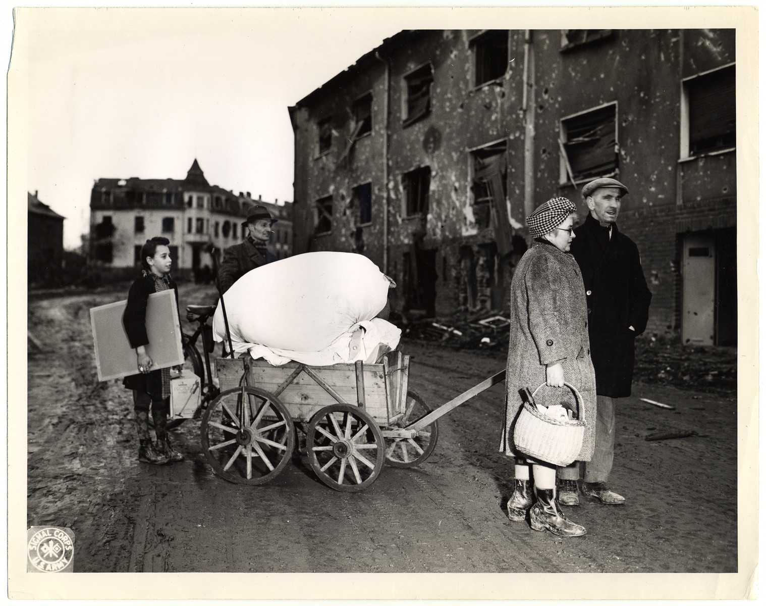 """German civilians move to new quarters after their own had been damaged beyond repair.  Original Caption: """"A Wurselen family moving to another house. His own was severely damaged beyond repair. The 'new' house was also damaged, but a few of the rooms could be made habitable."""""""