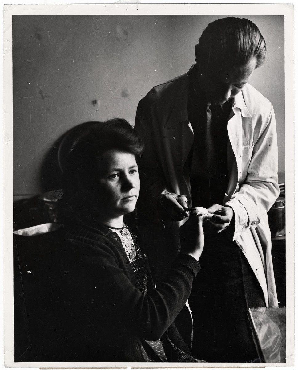"Orignial Caption: ""Dr. Alphonse Kujawski of Possnau, Poland, applies a sterile dressing to a finger wound suffered by 21-year-old Stephania Kawozynska, who deported in 1940 with her family from Poland to slavery in Germany.   When liberated, she was found with the badly infected finger, but amputation was avoided by careful treatment by the Allied doctors at the displaced persons center at Gnisnau Kasserne, a former German army post. All persons admitted into these camps are given thorough physical examinations and many are found to be suffering from a variety of ailments, including skin diseases. Liberated by the Allied armies in Germany, more that four million men, women and children, former slaves of the Nazi war machine, are free to return to their native lands as soon as repatiation machineray makes it possible. Meanwhile, these displaced persons are being gatehred from the fields, factories and roadsides of Germany by military government authorities and placed in camps where they are registered, fed, and clothed, sheltered and given medical attention.  Persons of almost a dozen nationalities, living in separate camps wherever possible, are guided along democratic lines in the operation of their communities. U.S. Army officials set up the displaced persons centers, guard the exterior of the camps and turnover the guidance problems to international teams representing the Unted Nations Relief and Rehibilitaion Administration. Once all the displaced persons are repatriated, UNRRA's job in Germany is finished, as it has nothing to do with Germans or Military activities.  The Governments of Belgium, Holland, France and Luxembourg have already brought thousands of their nationals home. By May 17, 1945, nearly 800,000 liberated prisoners-of-war and political deportees were evacuated from German camps. The group included 603,940 French, 130,140 British and 62,989 Americans. All the Americans, 100,000 Frenchmen and 119,000 Britans were evactuated by air."""