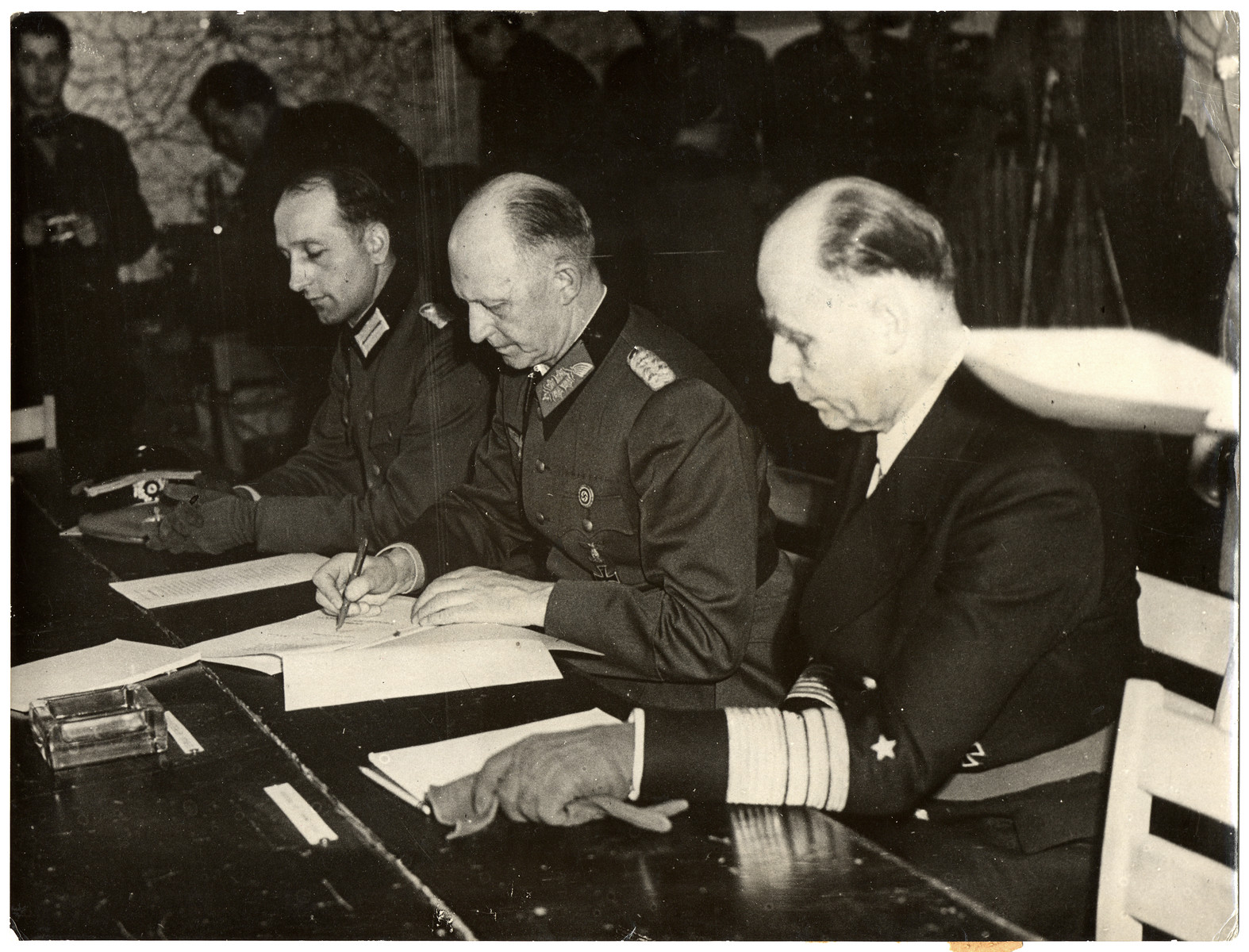 """Original Caption: """"Unconditional Surrender of Germany Signed at Reims; Colonel Ceneral Gustaf Jodl, German Cheif of Staff to Admiral Karl Doenitz, signed at 2:41 a.m. May 7, 1945, the document of unconditional surrender of Germany to the Allies in the war room at Forward German officers sign papers of surrender ending World War II.  Headquarters of Supreme Headquarters Allied Expeditionary Force at Reims, France. Under the instrument of surrender all German armed forces were bound to lay down their arms on all fronts. On General Jodl's left is Admiral Hans-Georg von Friedeburg of the German Navy, and on his right is Major Wilhelm Oxenius of the German General Staff. On extreme left is Colonel Ivan Zenkovitch, aide to Major General of Artillery Ivan Susloparoff who signed the document on behalf of the Soviet High Command."""""""