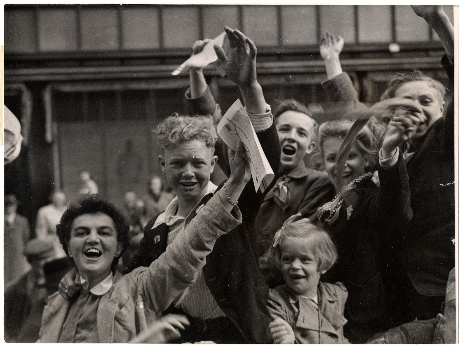 "Dutch civilians celebrate their liberation by Allied troops.  Original Caption: ""Victory crowds celebrating in the streets of Utrecht, Holland, were fired on by Nazi fanatics hiding in a building overlooking the parade. After a sharp skirmish, the Germans were captured by Dutch patriots and the celebration was resumed. Here, the cheering Dutch continue their celebrations of the Allied victory in Europe and their own liberation after five years under German occupation"""