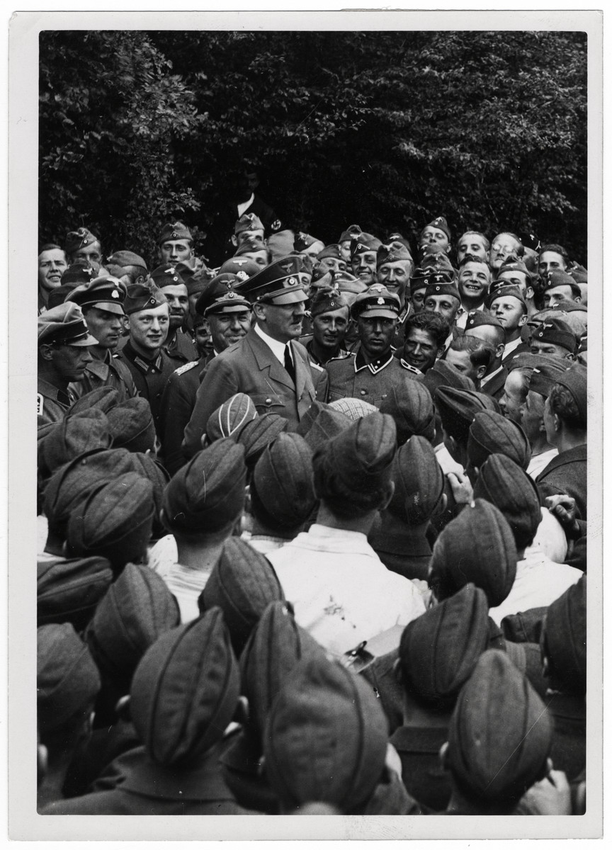 "Adolf Hitler meets with a large group of soldiers.  Original Caption: ""The leader among his soldiers"""