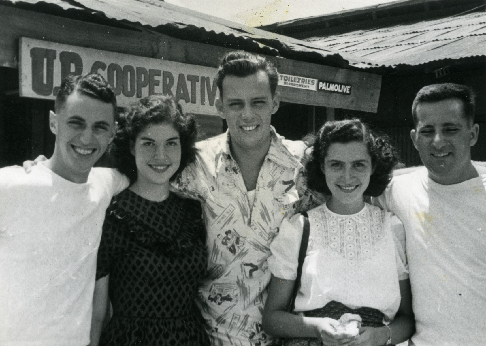 Jewish refugees and an American soldier pose in front of the American Army store in The Philippines.  Among those pictured are Becky Koenigsberg, Manfred Hecht and Margot Cassel.