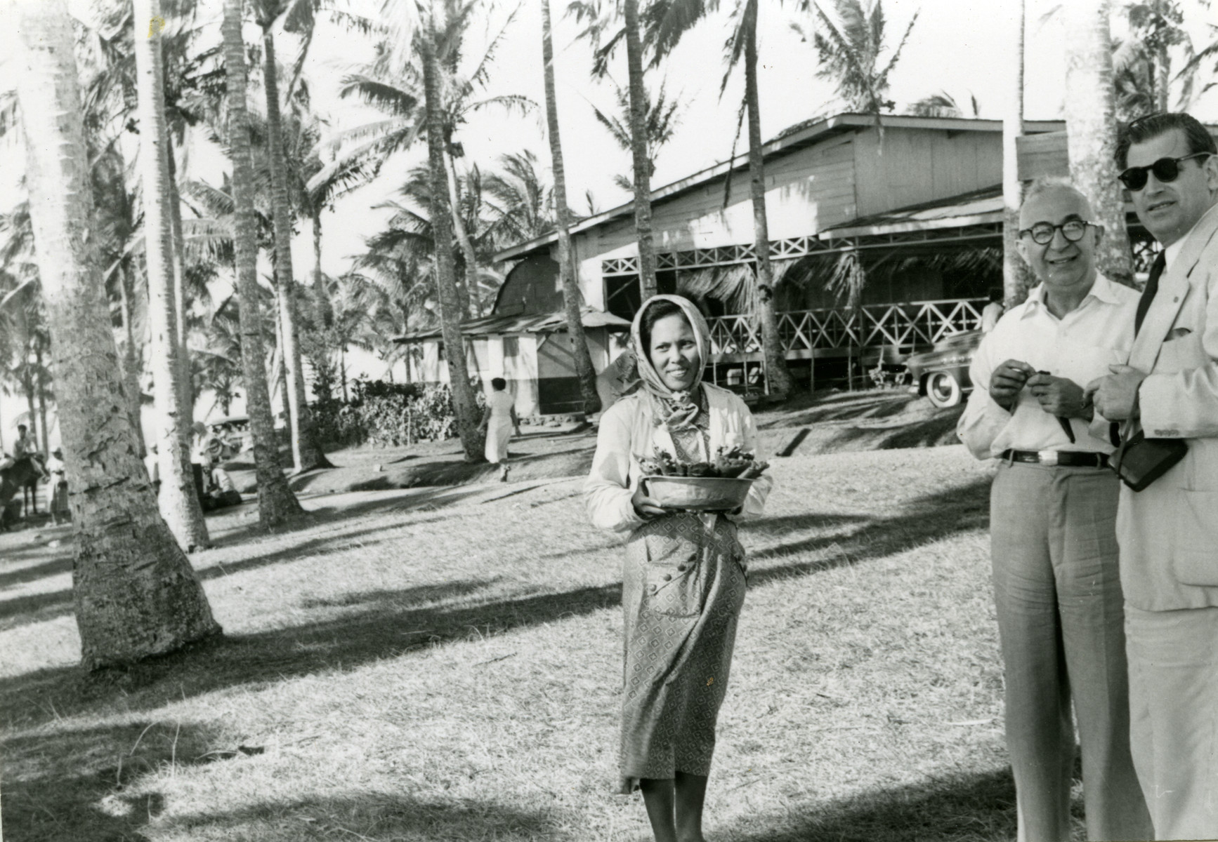 A Filipino woman carries a basket of food.    Dr. Harry Price is pictured on the right.