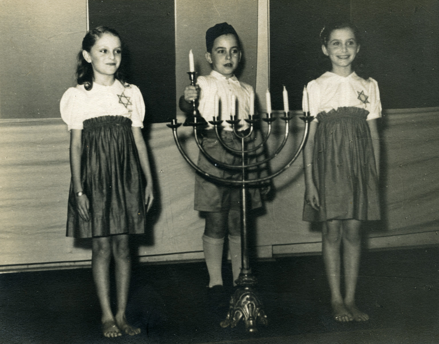 Jewish children light a menorah in a community Hanukkah celebration in Manila.  From left to right are Lotte Cassel, Werner Eicholtz and Margot Cassel.