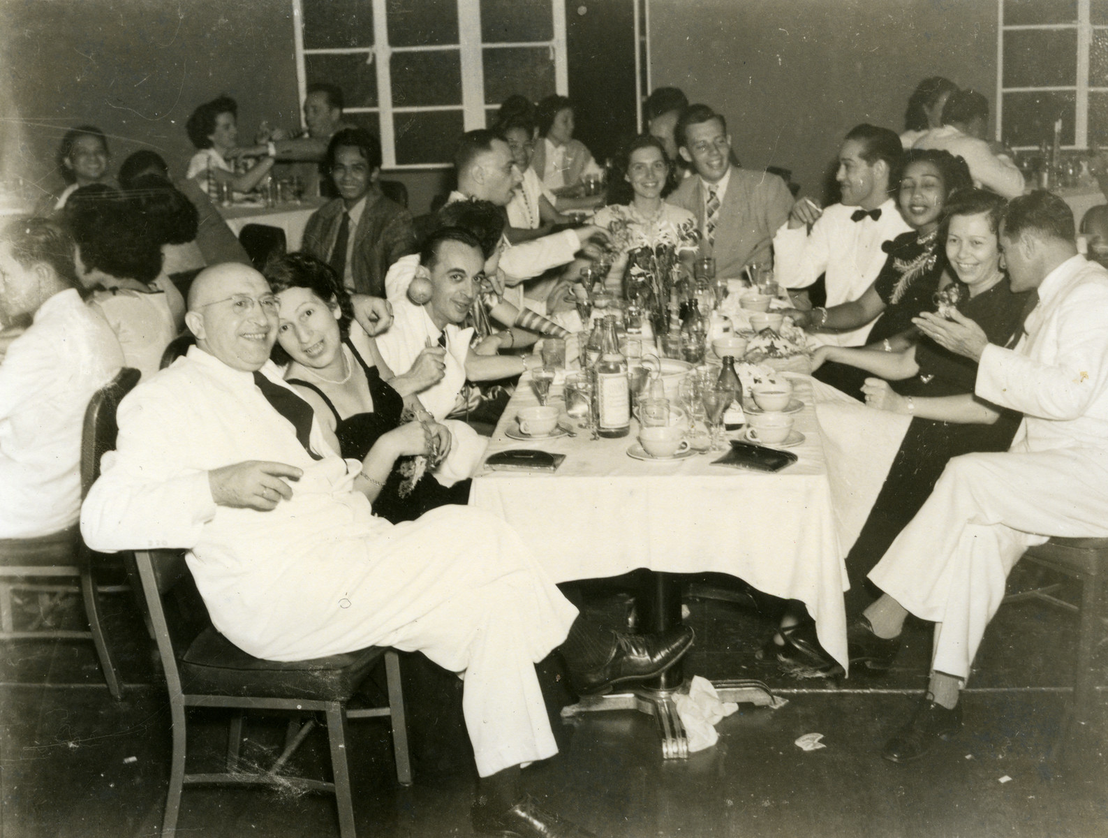 Jewish refugees and Filipinos gather for a celebration in Manila.  Seated at the back of the table are Margot Cassel and Manfred Hecht.  Seated at the front left are Saul Cassel and Mrs. Sueskind.  Seated on the front right are Erna Cassel and Mr. Sueskind.
