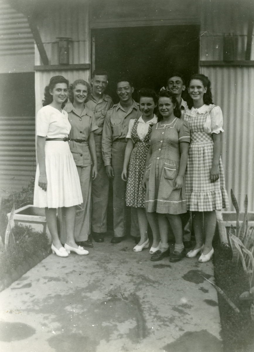 Group portrait of Jewish refugees in Manila together with an American army chaplain.  From left to right are Margot Cassel, Lotte Cassel, Manfred Hecht, Chaplain Abraham Feldman, Ruth Greenfeld, Margaret Michwinsky, Sigi Hellman and Gitta Welisch.